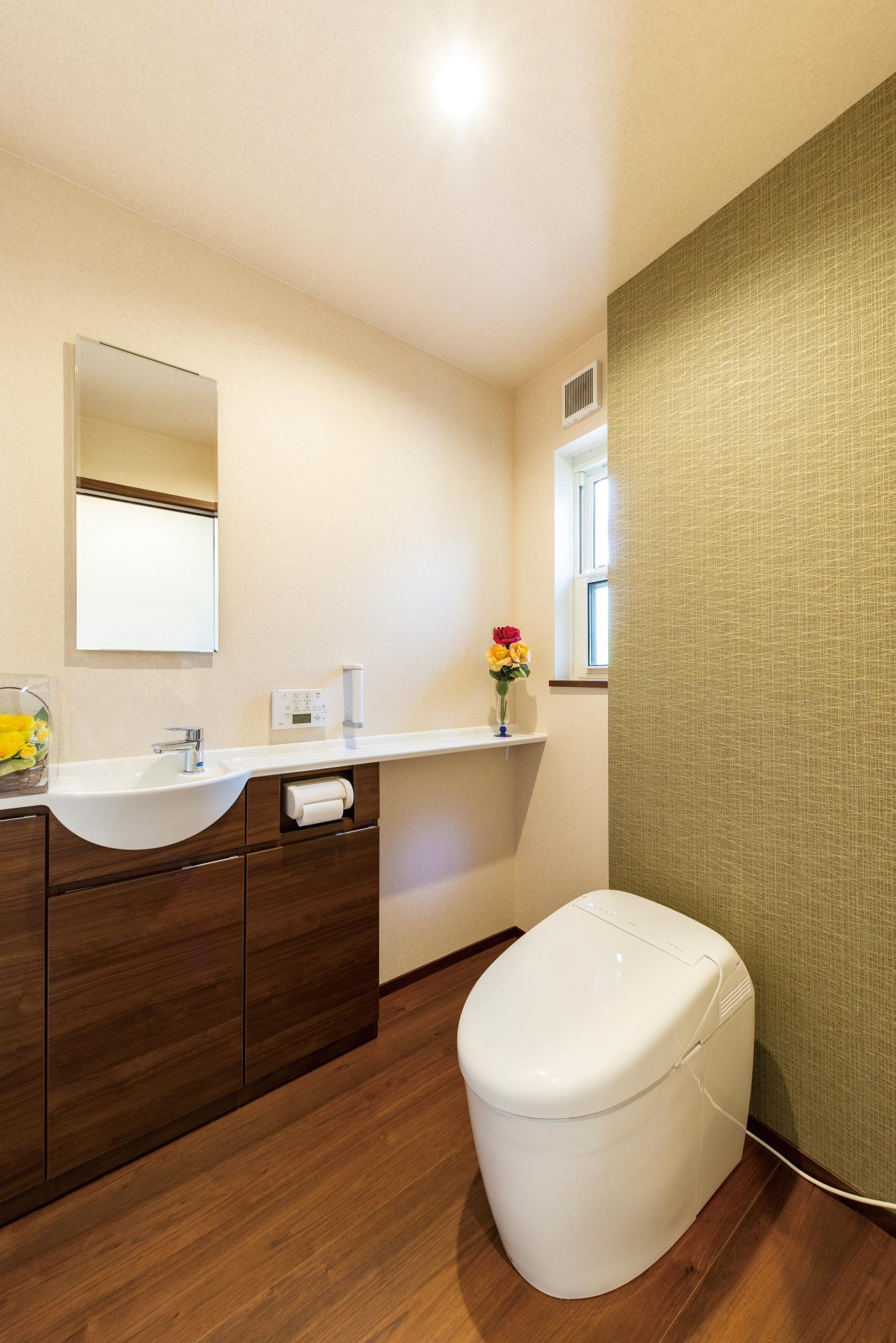 ゆとりの広さを持つ1階のトイレは、アクセントクロスと木質感の効いた内装で、明るく落ち着いた雰囲気に
