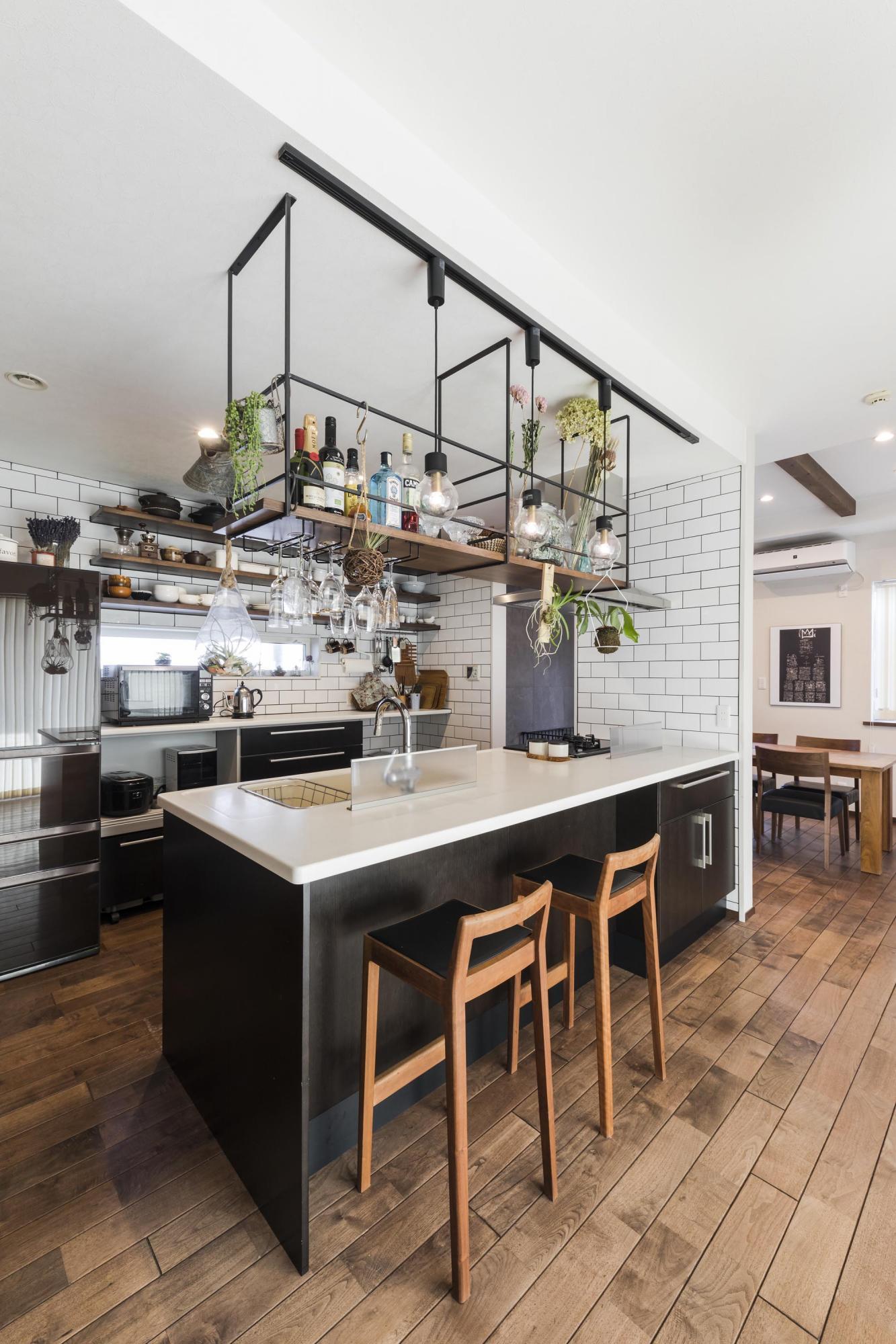 ダイニングに行きやすいように壁の一部を取り払い、動線も見直すことで使いやすいキッチンに。カウンター上部にはお酒などを並べることができる吊り棚をつくり、夜はバーコーナーとしても楽しめる