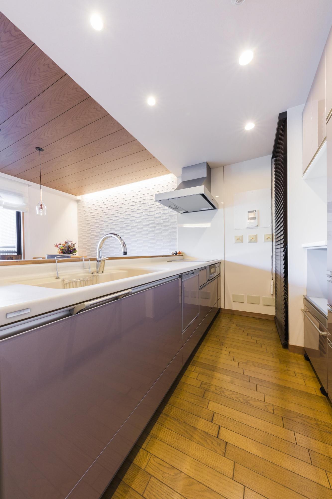 ブラウンを基調に、質感溢れるキッチンに。ダイニングの壁には調湿・消臭効果があり、空間のアクセントにもなるエコカラットを採用している
