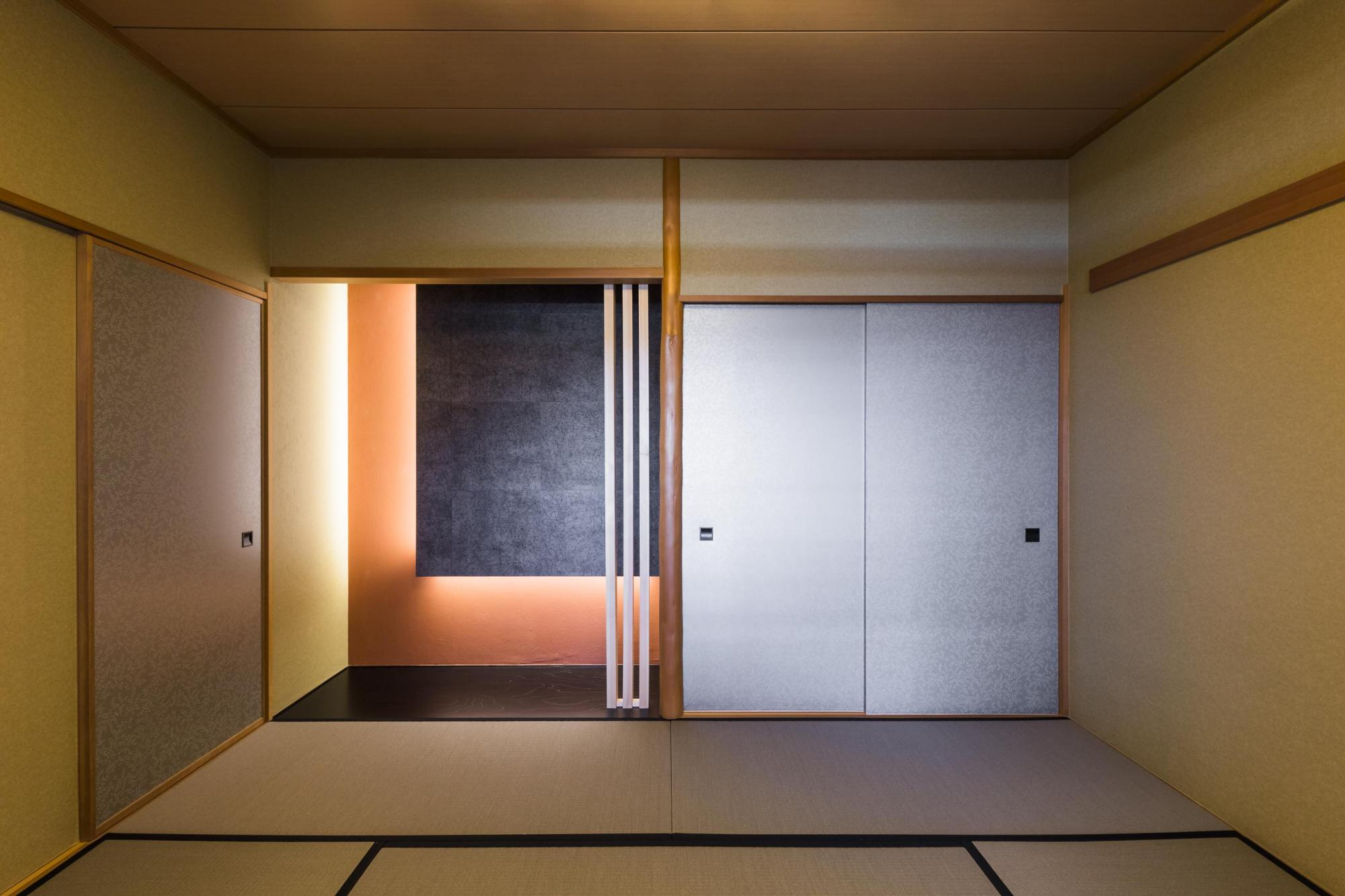 リビングに隣接した大壁の和室。床の間の一面にダークな色のクロスを採用し、間接照明が映える空間に。格子スクリーンがアクセントになっている