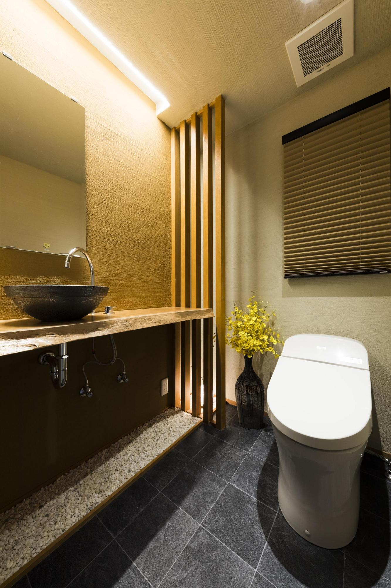 格子のスクリーン、陶器の手洗いボウル、玉砂利などで、和の雰囲気溢れるトイレに