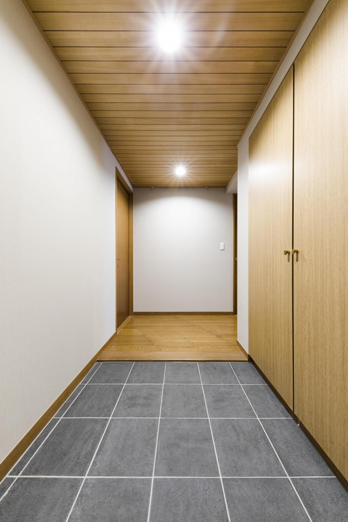 玄関ホールは、ダウンライトを設けた木貼りの天井がやさしく迎えてくれる空間だ