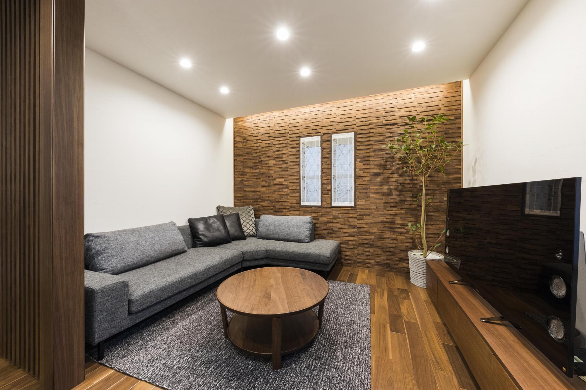 元々キッチンがあった場所は、間接照明とウッドパネルで演出したリビングに。インテリアの色味は、最初に床材をウォルナットに決め、家具やカーテン、照明などトータルにコーディネート。統一感があり、木質感溢れる空間となった。壁に採用したウッドパネルは、Wさんがショールームでひと目惚れした素材を採用している