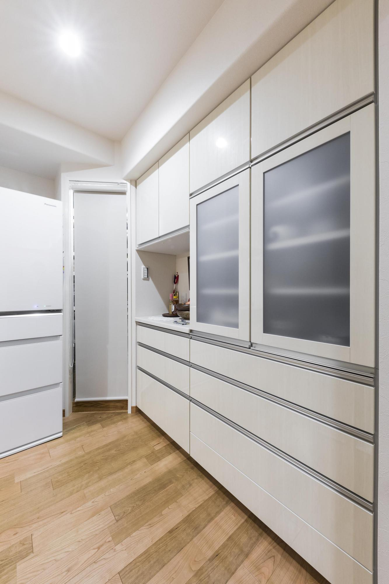キッチンのカップボードの奥には、食品などを収納しておけるパントリーも設置。以前のキッチンにはなかった空間なので、とても重宝しているという。白を基調にしたカップボードの面材が、空間をより明るく演出している