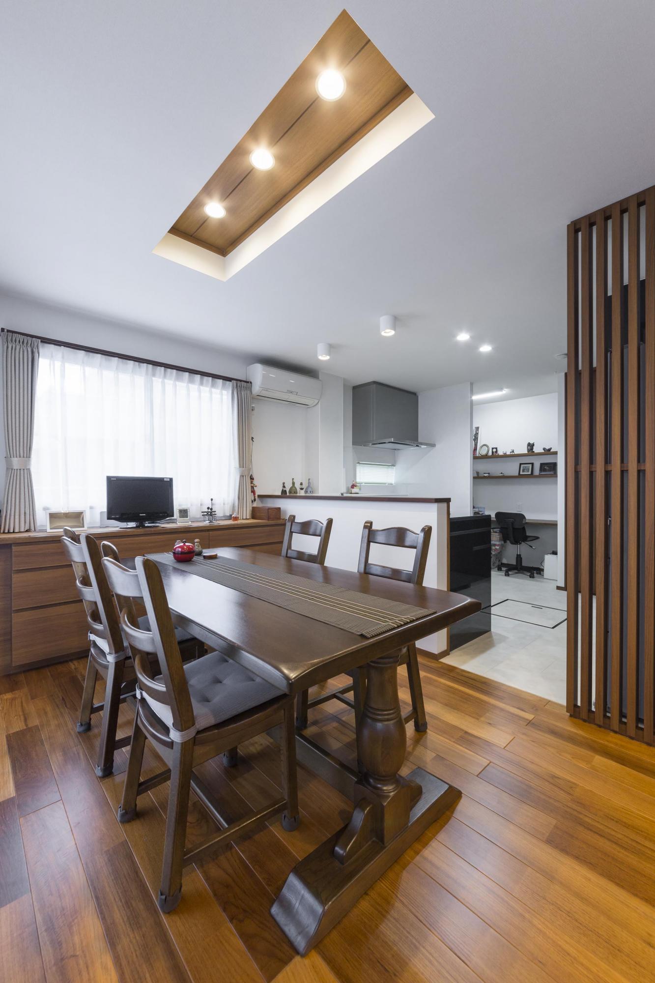 ダイニングの照明は、テーブルの真上部分に埋め込み、デザイン性をもたせた。窓側にはカウンター収納を造作し、正面奥には家事室を設けている。