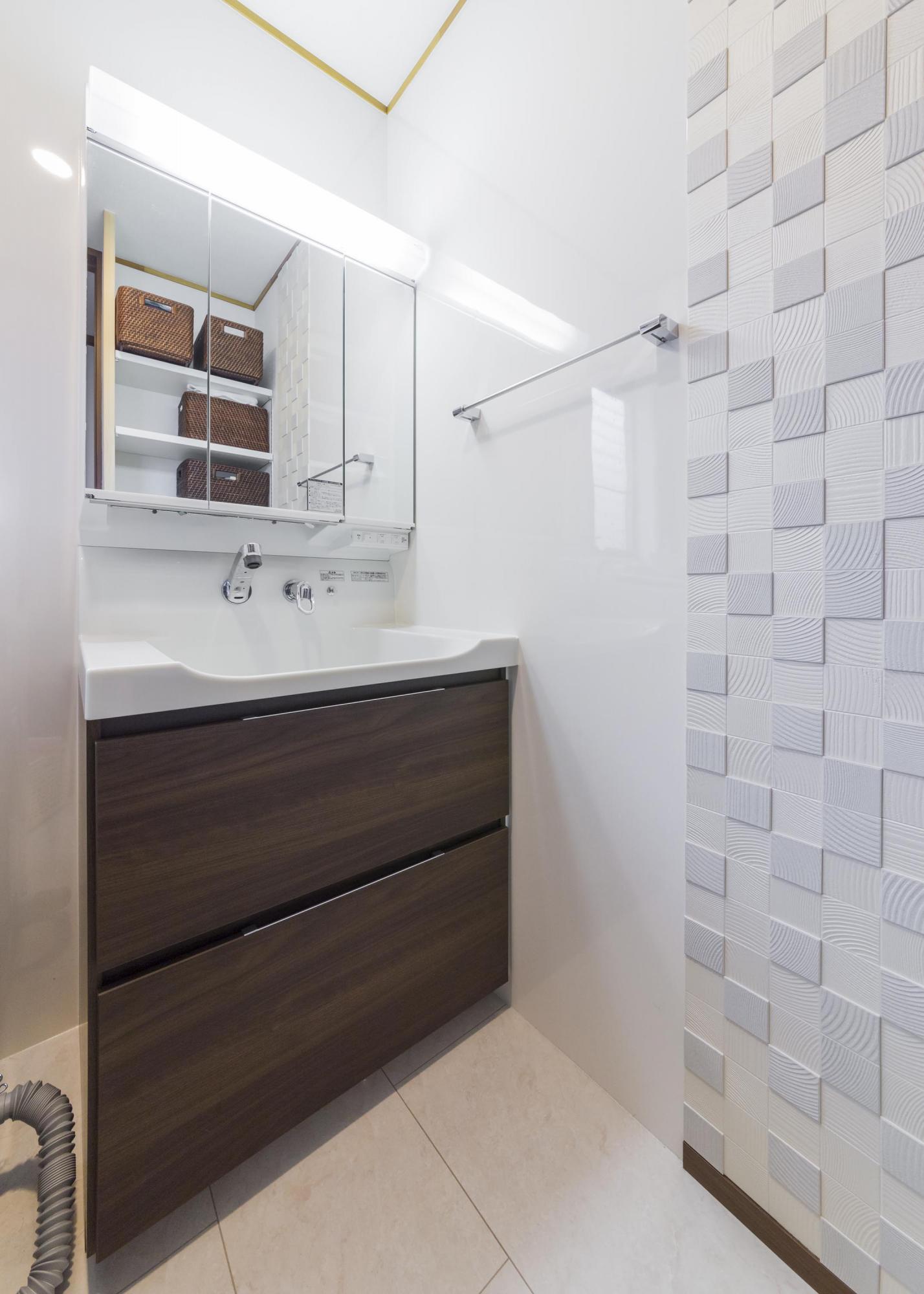 洗面室の壁には湿気などを吸収するエコカラットを採用。洗面化粧台の向かい側には収納棚を設け、タオルなどをさっと取り出しやすくした。