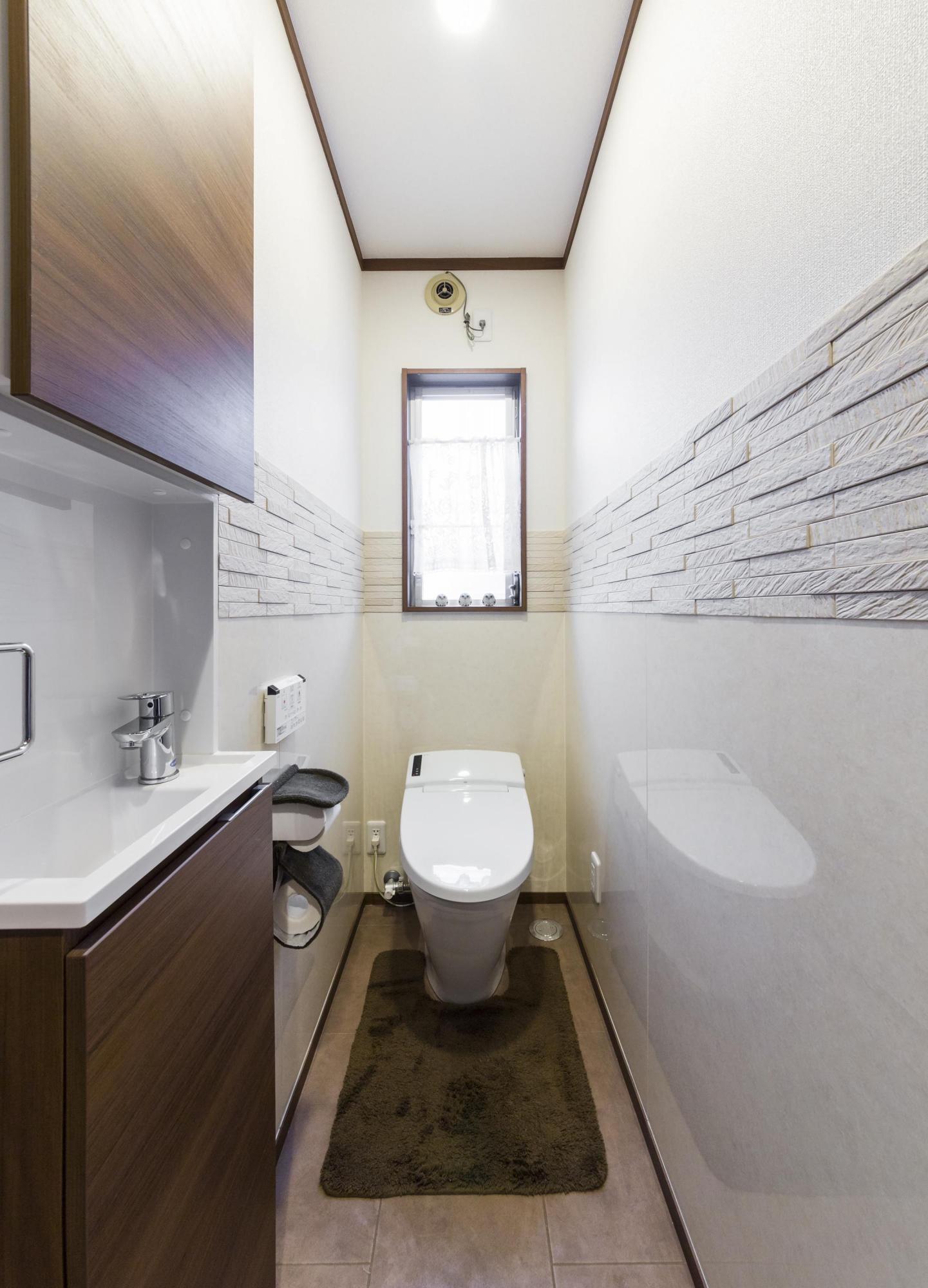 トイレの入り口の段差を解消し、壁の一部にはエコカラットを貼って心地良い空間に。新たに収納スペースと手洗い場も設けた。