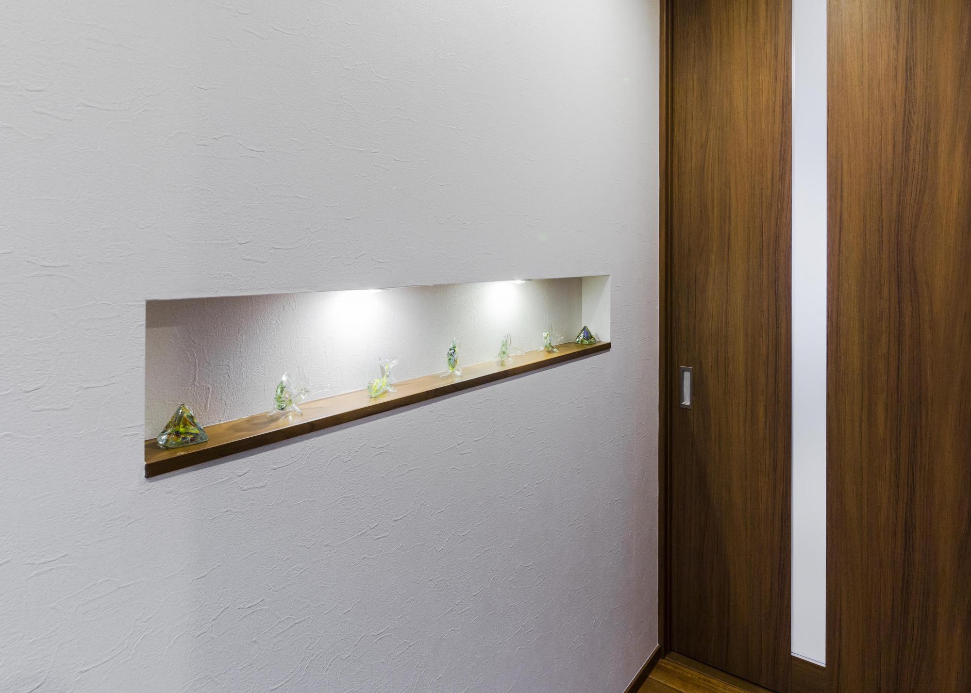 リビングの入り口前の廊下壁面に埋め込み型の飾り棚を造作。思い出の品を飾って楽しんでいる
