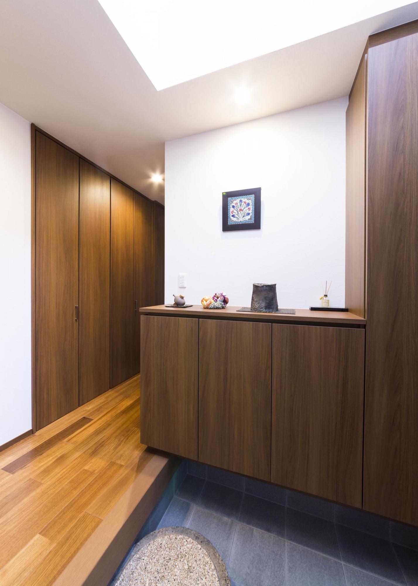 新たにシューズクロークを設置した玄関。その向かいには大きな物を収められる収納庫が。廊下の左壁の厚さを活用して食品庫も設けた。