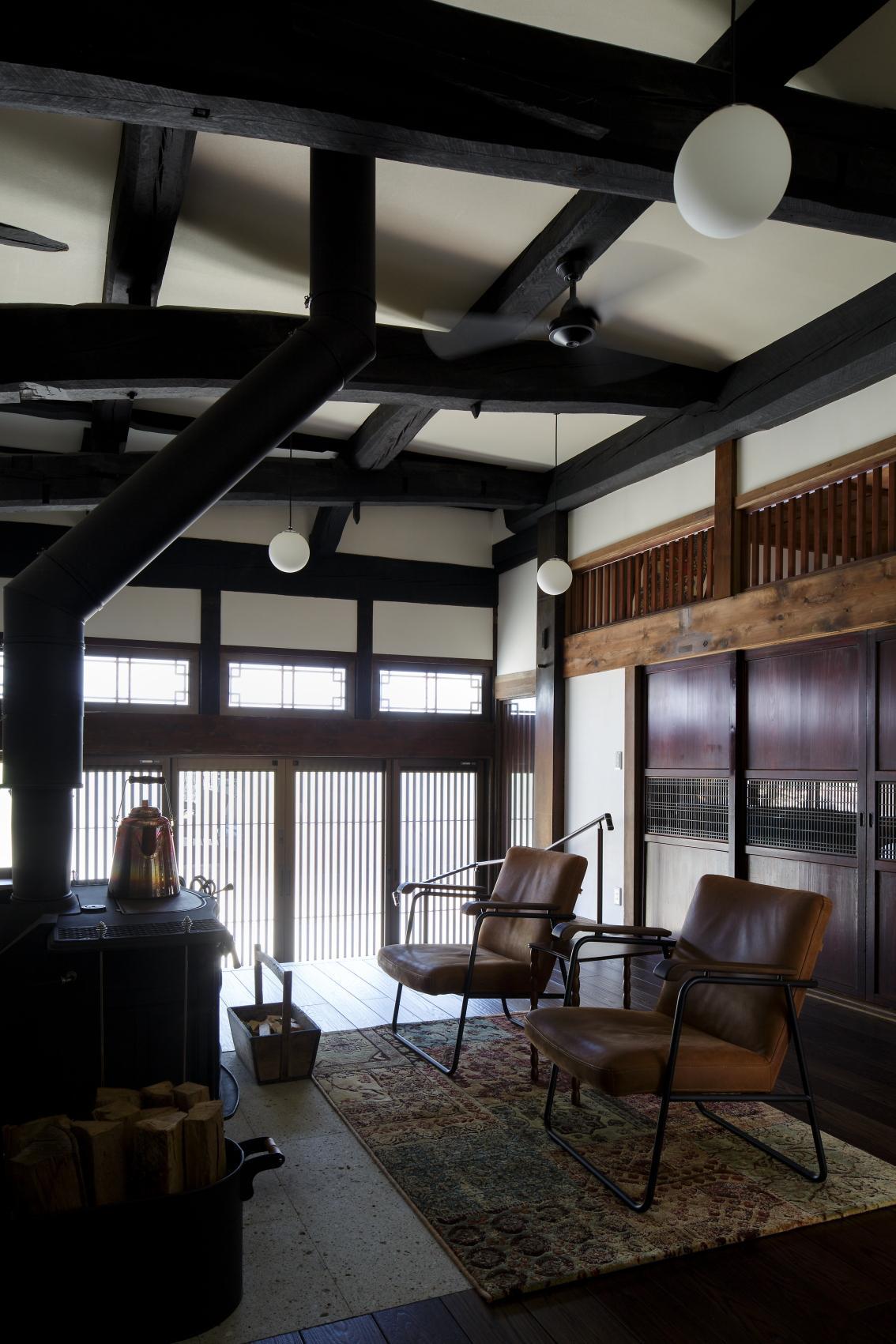 天井を取り払い、梁を現した開放感あふれるホールに薪ストーブを設置。床材は古式ゆかしい空間にしっくりとあう落ち着いた色合いのなぐり調フロアを使用した。