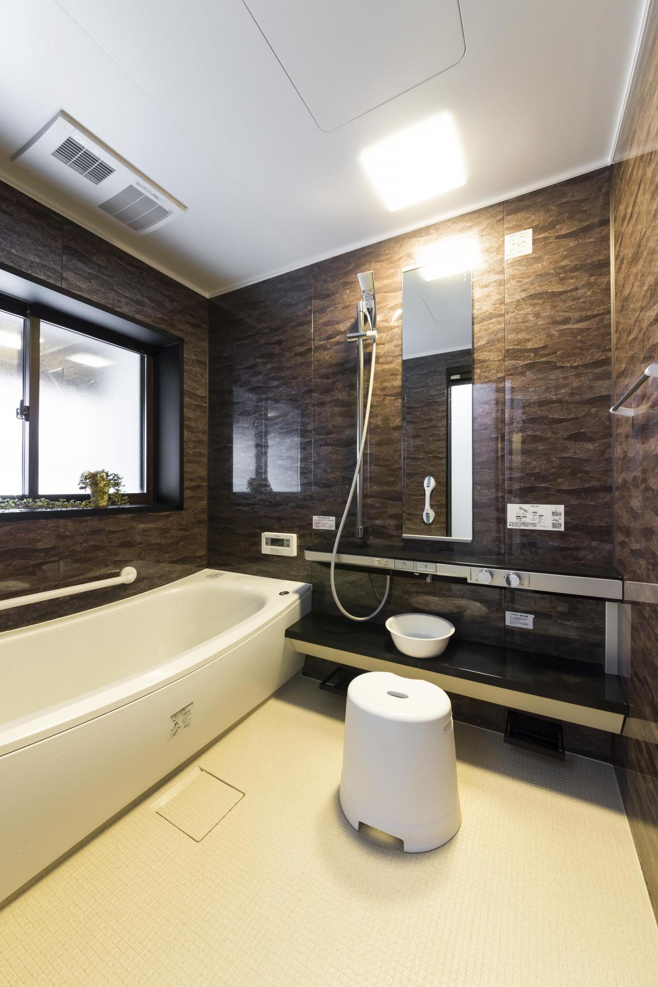 ブラウンとホワイトのシックな色づかいで仕上げたバスルーム。窓を大きくとり、洗い場のスペースも広げた。