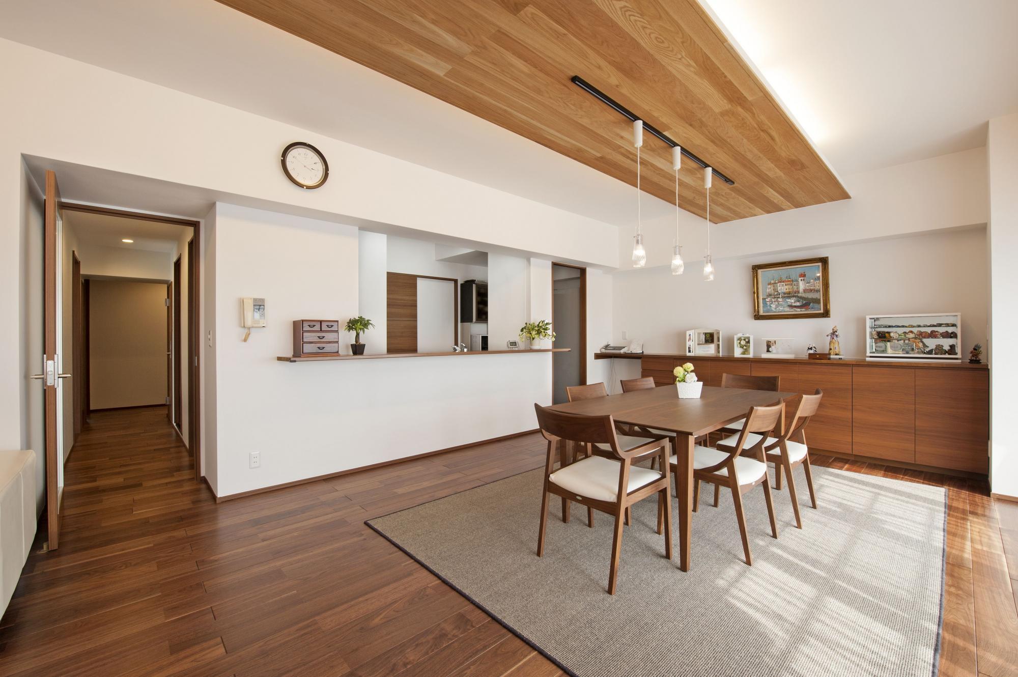 リビングへと続く飾り天井には、ガラス製のペンダント照明をご提案。木のカウンター収納も造作している。