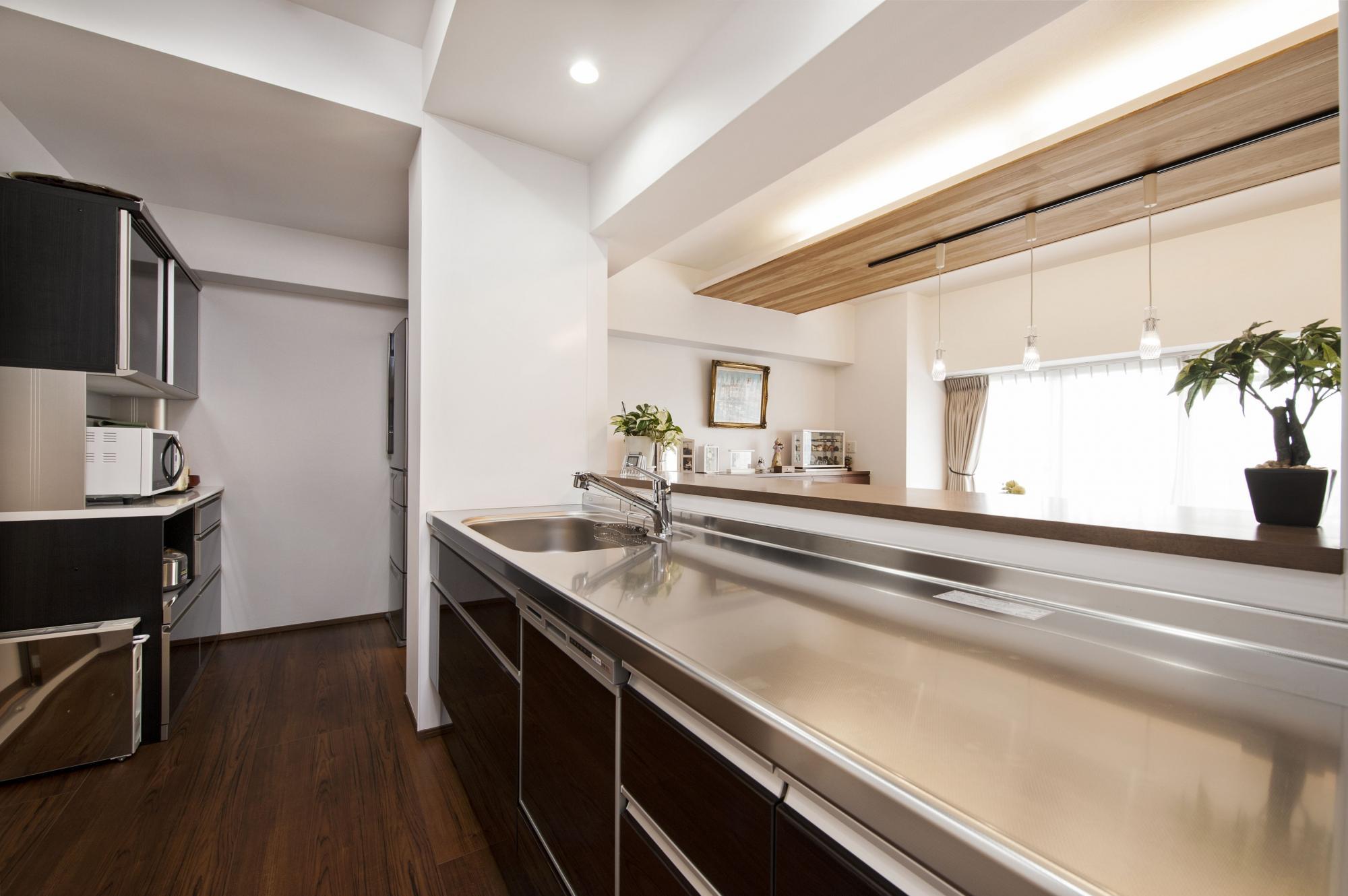 吊り戸棚を取り払い、開口部を大きく広げた対面式のキッチン。鏡面仕上げの扉が美しいシステムキッチンはショールームで選んだ。