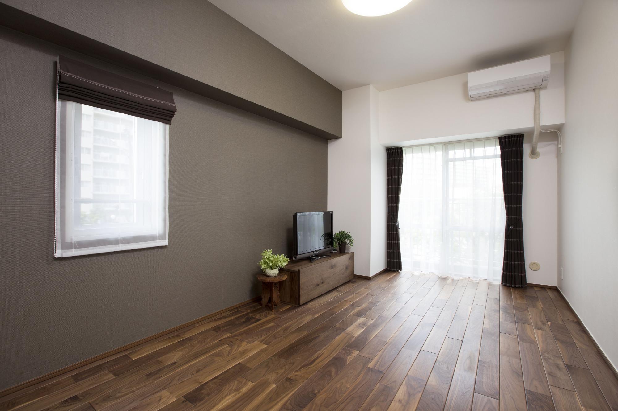 洋室の床も18mmのウォルナット無垢材。壁はグレーのアクセントクロスでシックに演出し、カーテンは室内の雰囲気にあわせて選んだ。