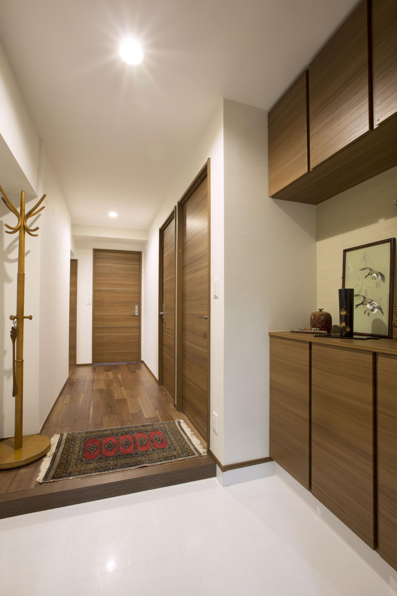 隣接する洋室側の収納スペースを取り込んで、床面積を2倍近く広げた玄関。タイル床も光沢のある白色に貼り替えて明るく仕上げた。