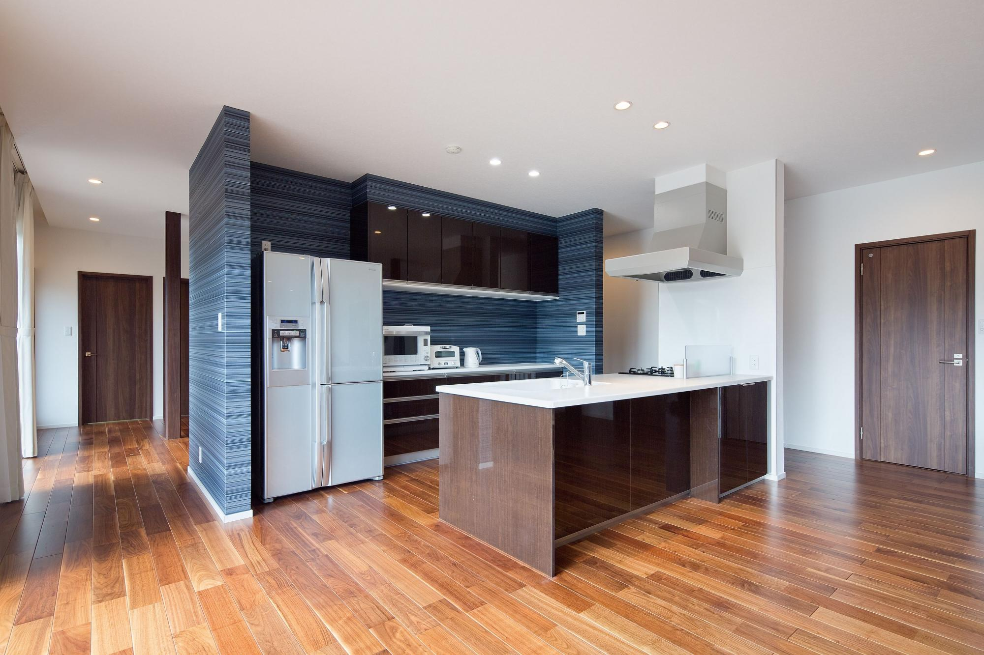 LDとひと続きになったキッチンは、奥様の希望でお子様を見守りながら家事や料理ができる対面式のペニンシュラタイプに。背面にはモノが置けるカウンタータイプの収納棚を設置し、キッチンの近くにはパントリーも設けた。