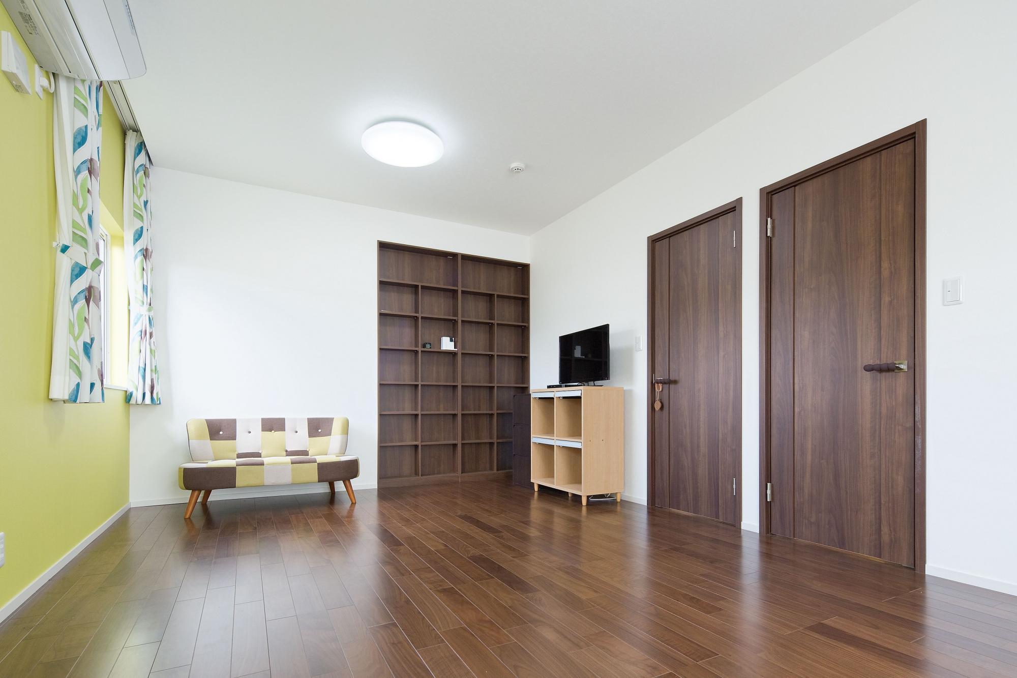 本棚は造作し、イエローの壁をアクセントにした子供部屋。将来間仕切りを付けて二人のお子様がそれぞれの部屋として使えるように2ドアに。玄関からリビングを通って必ず両親と顔をあわせることができる動線を考えた。