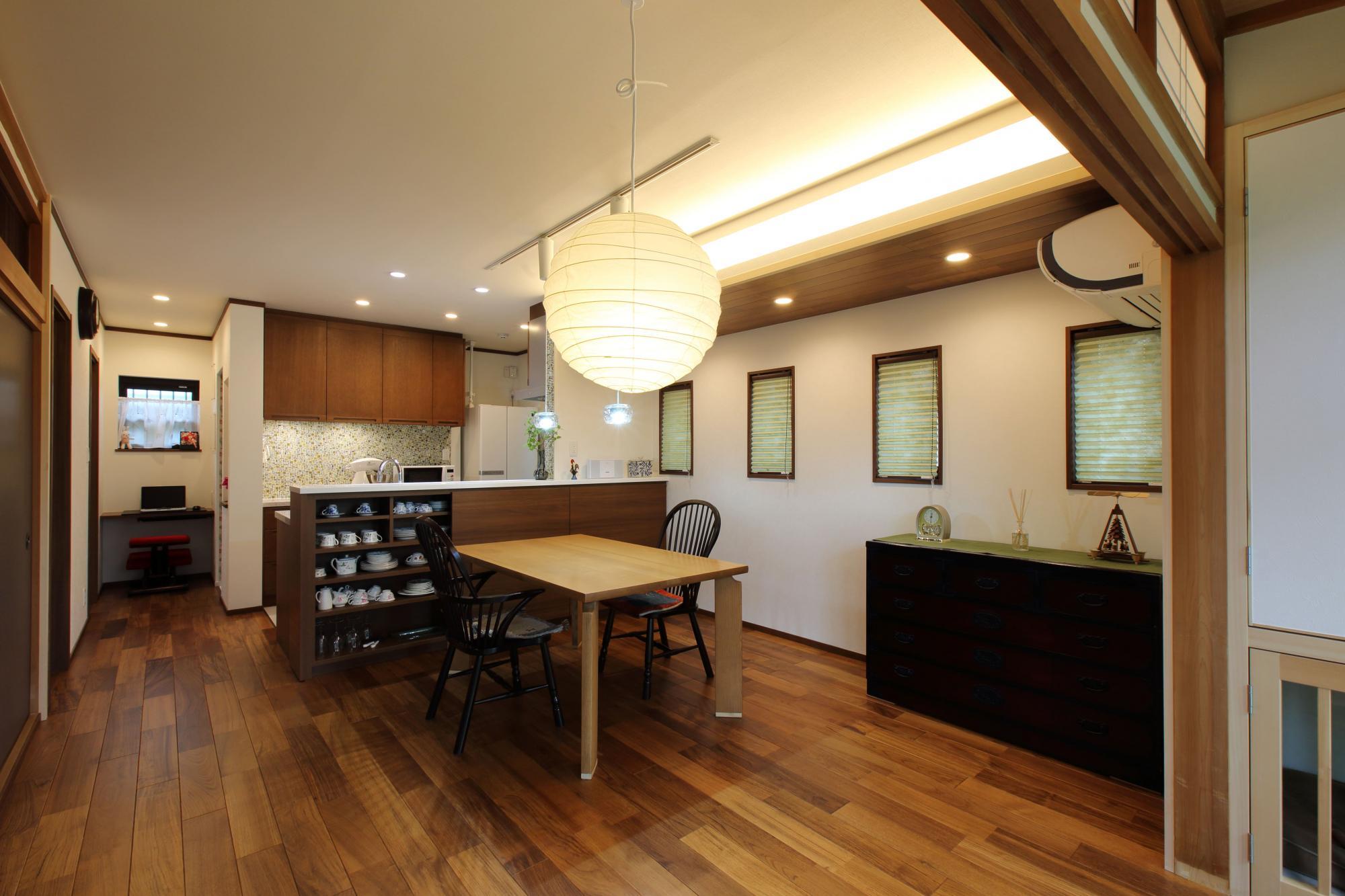 ニ間続きの和室のひと部屋をLDに変更。ひと続きになったLDのチーク材のフロアとキッチンのタイルフロアは床暖房対応に。雰囲気のある空間に演出するために、押し入れだった部分を下がり天井にし、4つの縦すべり出し窓を設置。
