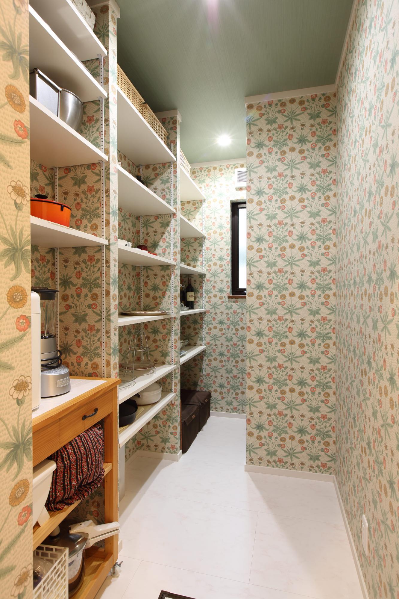 収納スペースを十分確保した食品庫の壁面には、奥様のご要望で有名デザイナーのクロスを張り、明るい雰囲気に演出。
