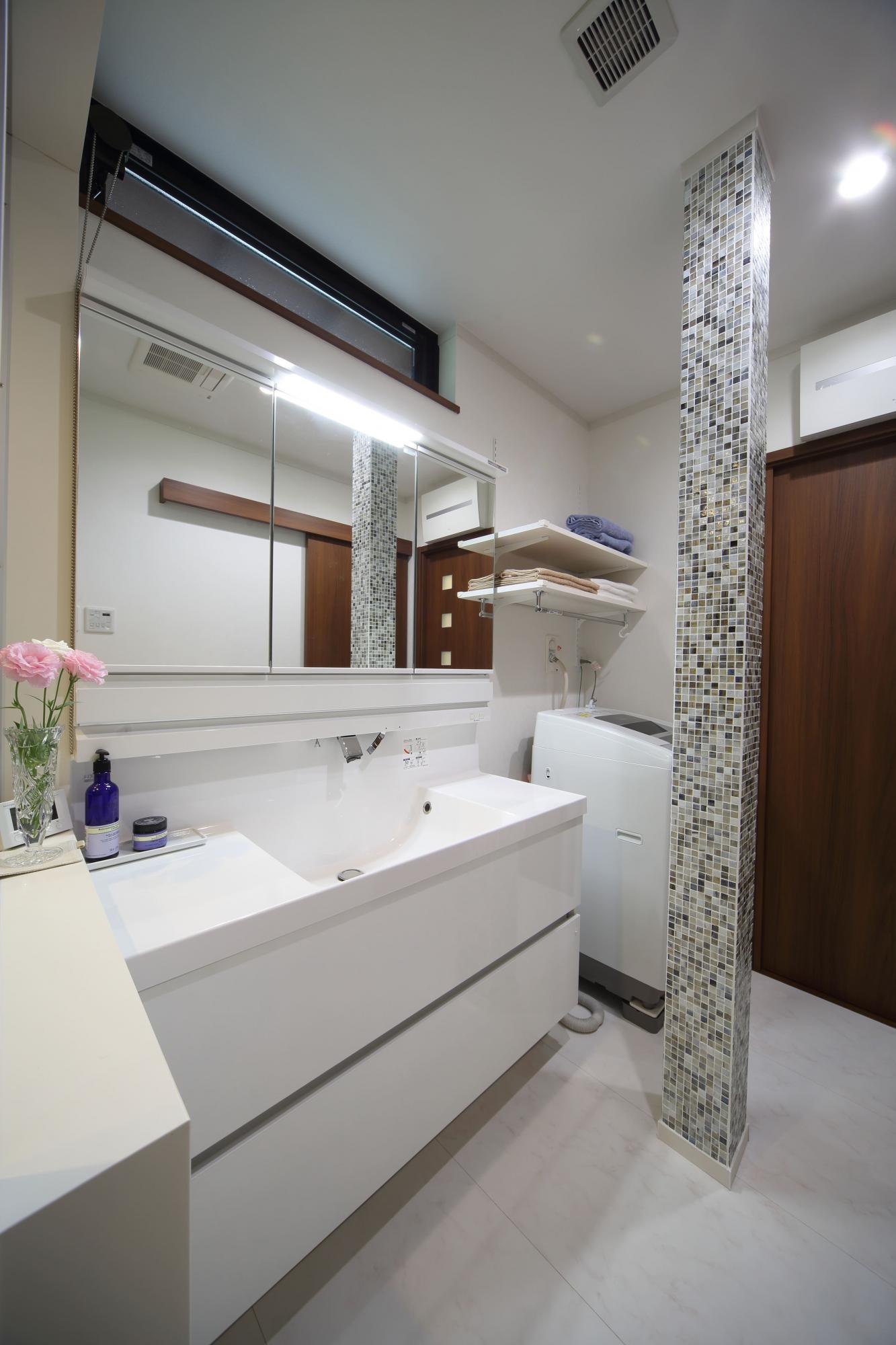 洗面室の抜けない柱にはキッチンと同じモザイクタイルを張り、空間のアクセントに。洗面上部には横長の通風窓を設けた。