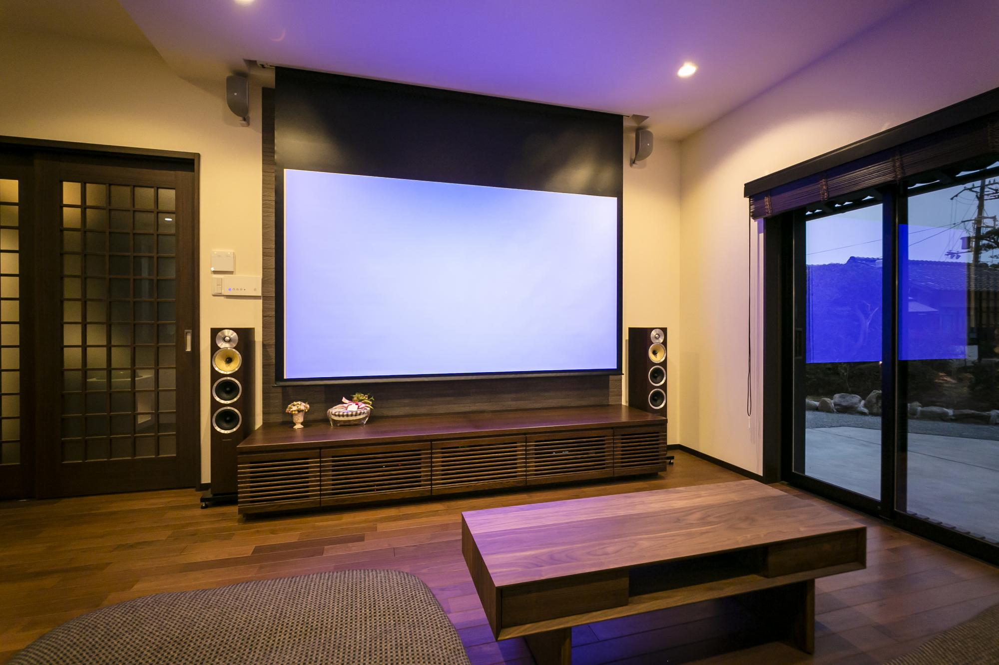 リビングはご主人自慢のホームシアタースペース。迫力ある大画面のスクリーンと臨場感あふれる音響設備を備えた。 LDの梁の部分には最新設備のプロジェクターが。リビングとダイニングとの間に一部壁を設けて空間をゆるやかに分離している。