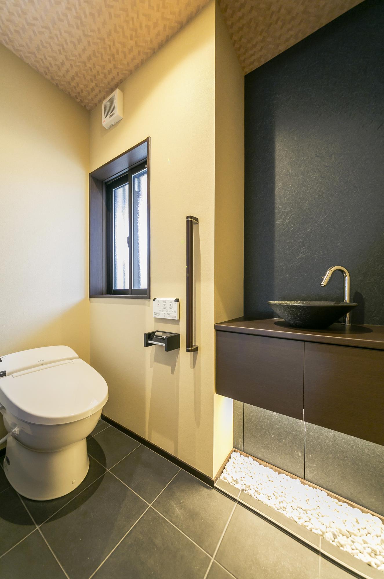 トイレもバスルーム同様、母屋に配置。手洗いカウンターには床から浮いたようなデザインのフローティングファニチャーを採用し、足元にフットライトと小石を配して雰囲気を出した。また高齢のお母様のことを考えて手すりも取り付けている。
