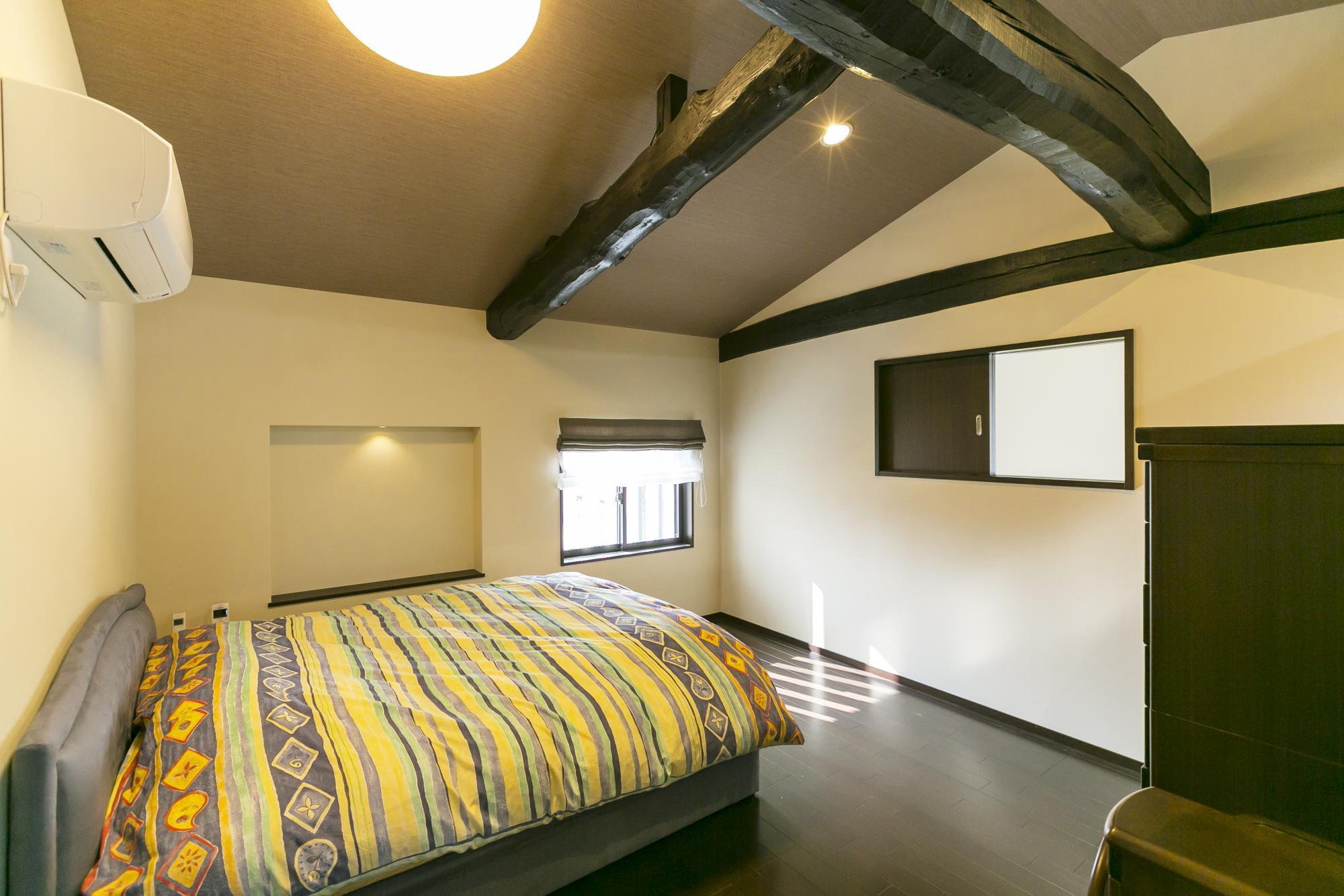 2階はご夫婦の寝室。天井が低くて圧迫感があったため、天井梁を見せて開放感と木の温もりが感じられる空間に仕上げている。