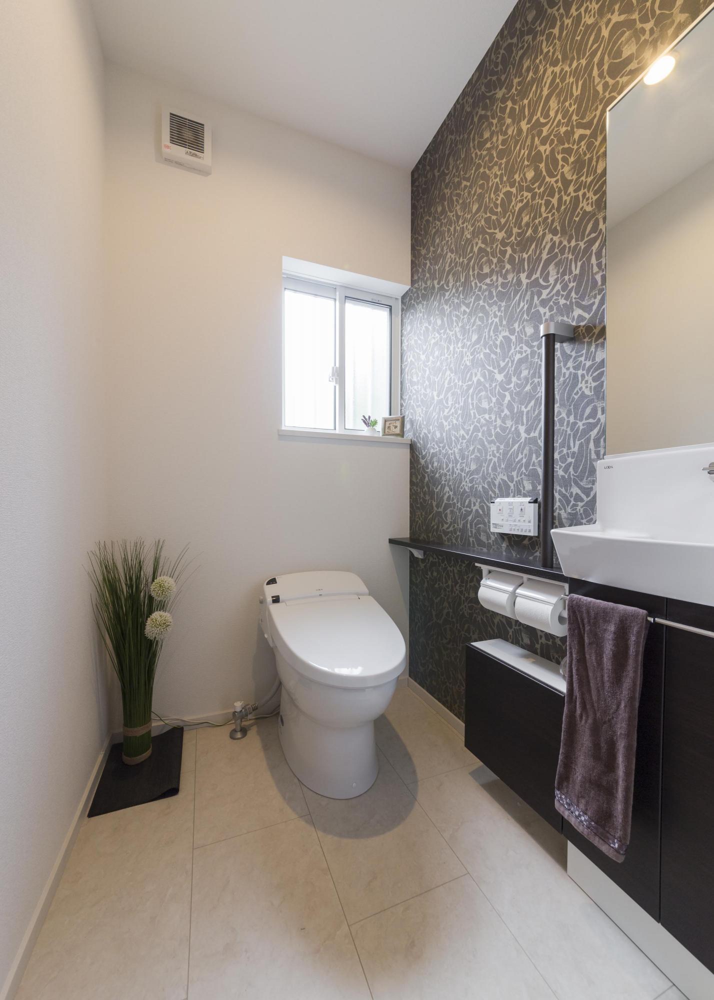 トイレは移動して向きを変えた。壁面にはモダンなアクセントクロスを貼り、ミラー付き手洗いカウンターも設けている。
