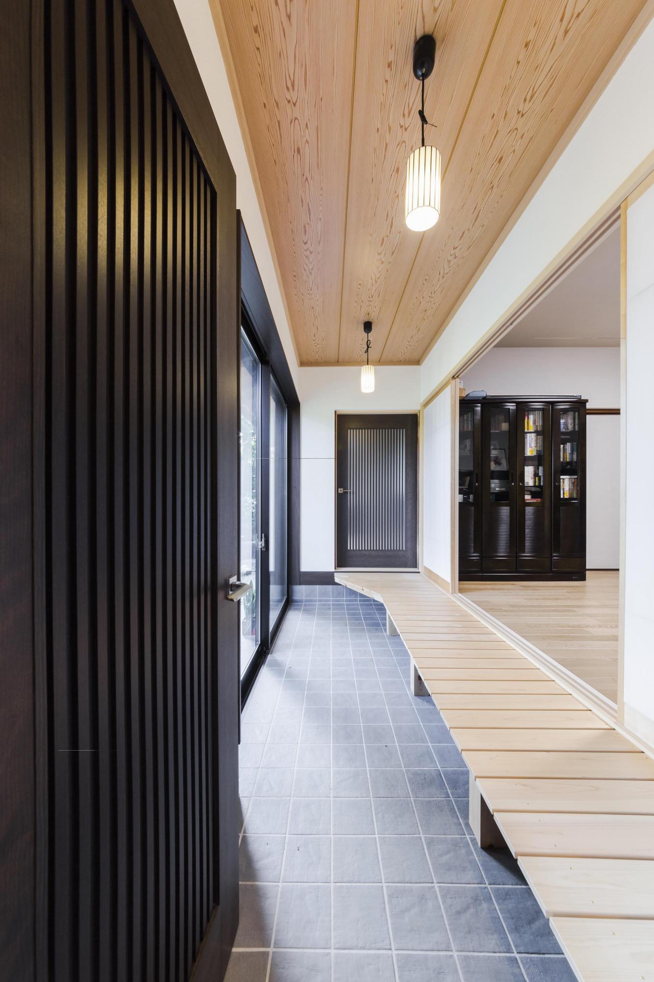 玄関からつながるタイル貼りの土間。檜で造った縁側からお客様は直接部屋へ上がることができる。真正面の扉を開けると既存の広縁へと続く