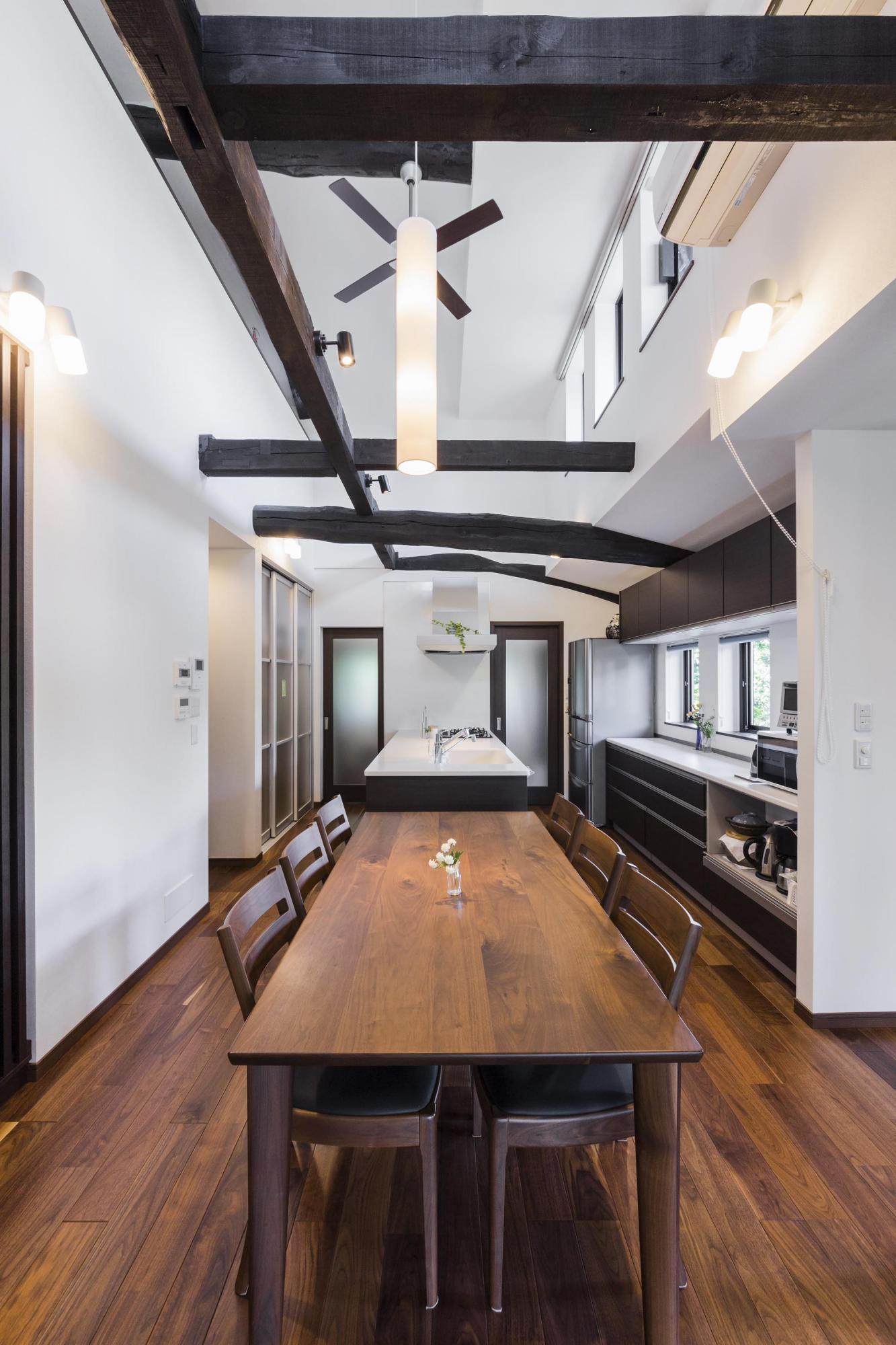 ダークなブラウン系のウォルナットフロアには床暖房を設置。写真のダイニングテーブルは床の色にあわせて選んだ。