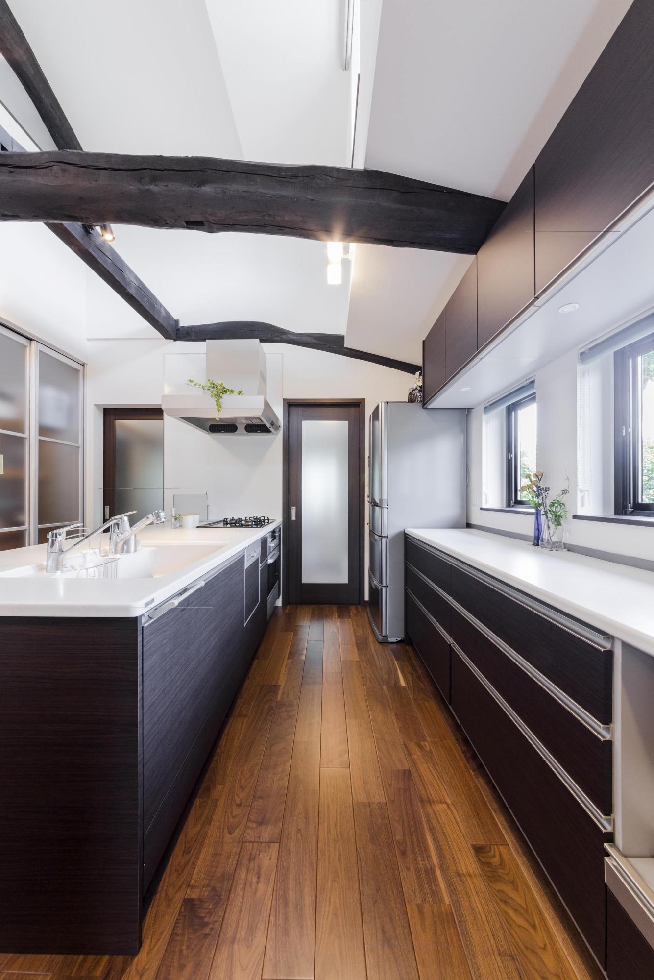 キッチンはアイランド型を採用。右壁には十分に収納量を確保したカップボードを。左壁には物入れを設け、既存の食器棚を収められるようにした。正面の2つ扉は勝手口へと続いている。