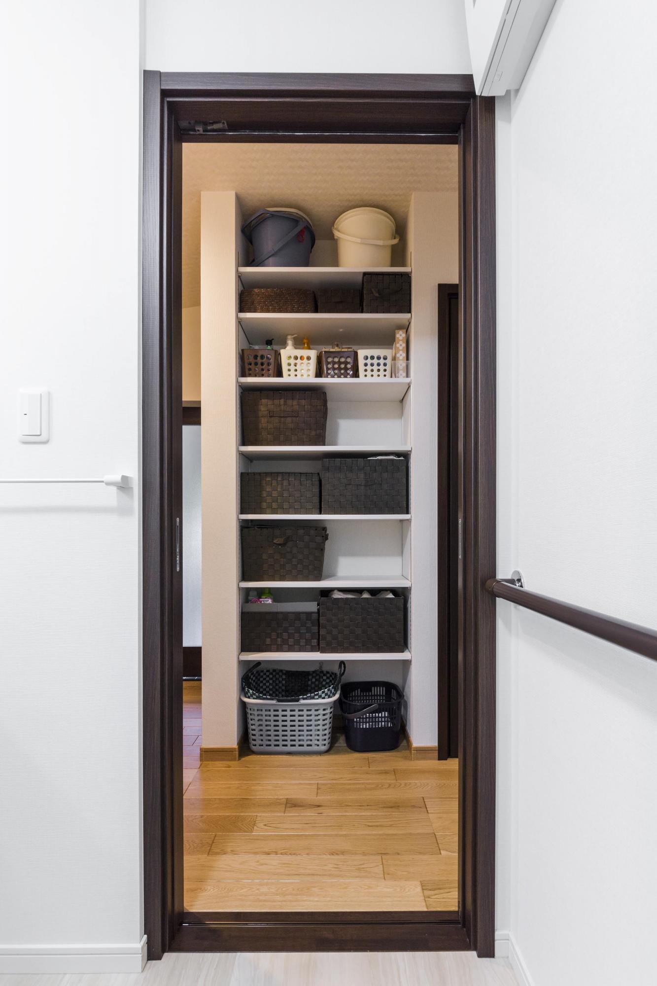 洗面室やトイレに面した廊下の柱を利用して、7段の可動棚を造作した。