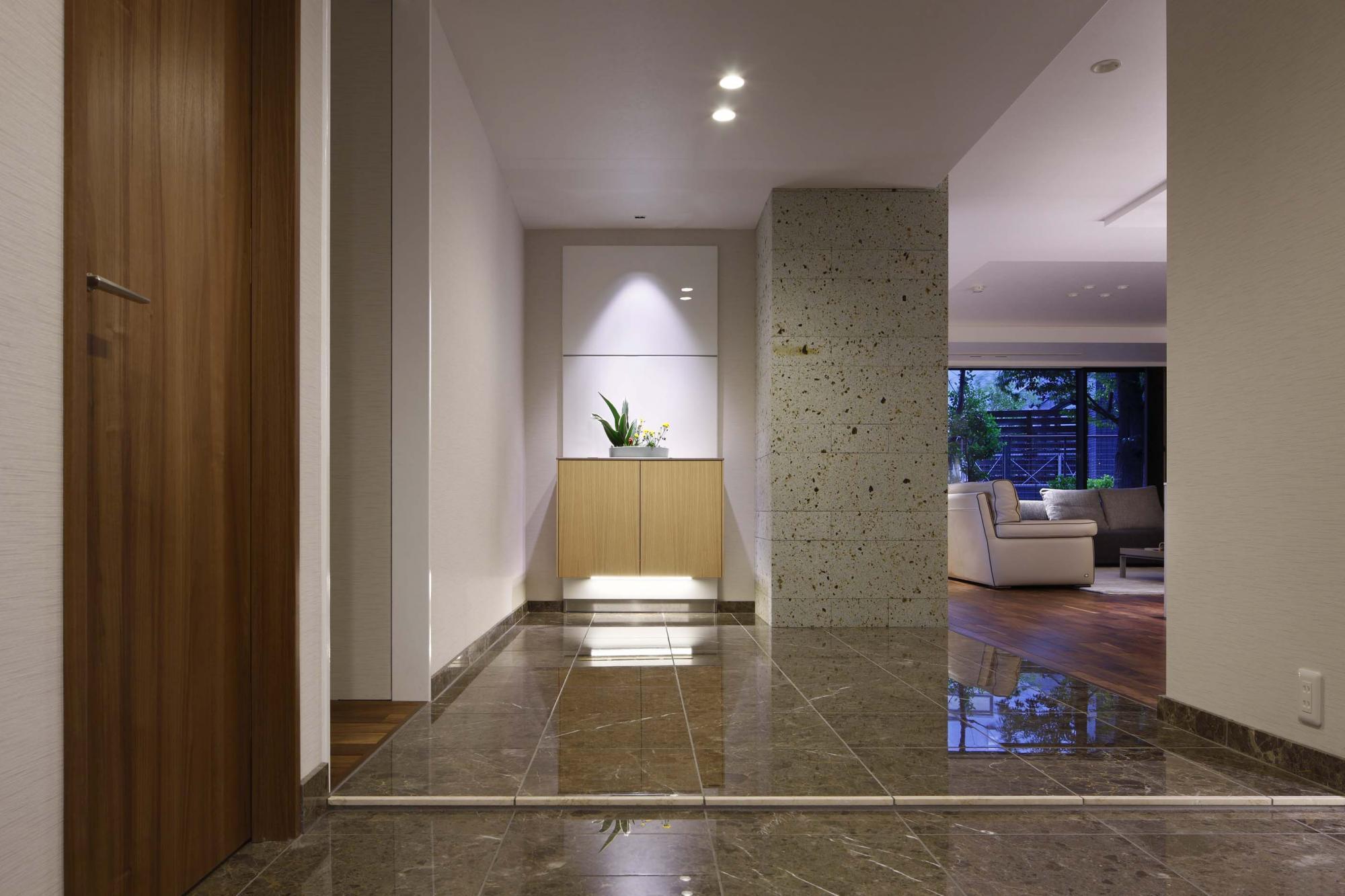 玄関に入ると光沢のあるグレーの大理石の床がホールまで続く。正面の壁には当社オリジナルの床から浮いたような収納カウンターを設置。下から間接照明を照らして美しく演出している。