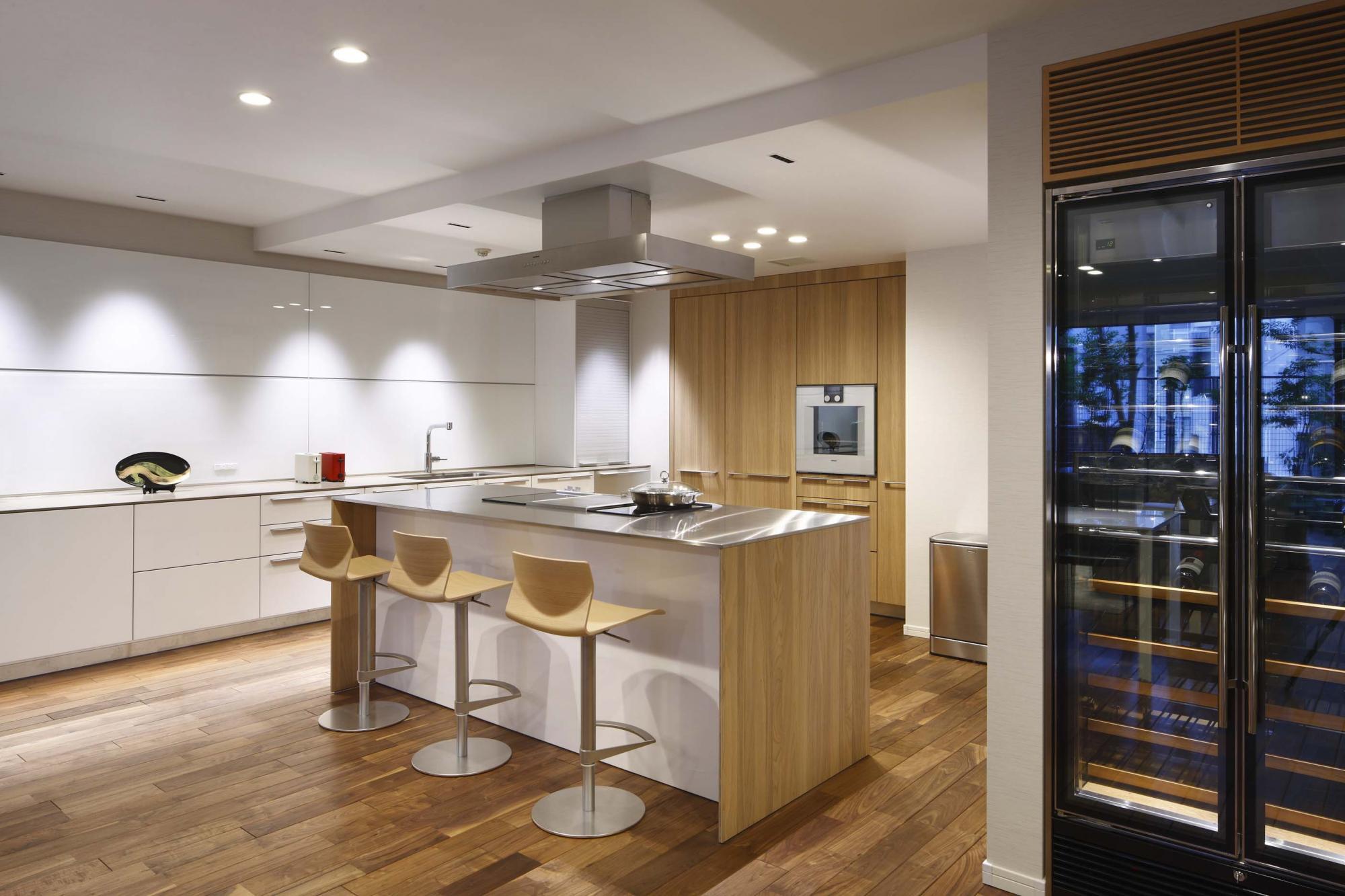 キッチンカウンターはドイツ製のアイランドタイプを採用。シンクは左奥の白い収納カウンターに設置。オーブンから食洗機、大型冷蔵庫に至るまでビルトイン式のシステム収納に収められている。 キッチン横のスペースには、F様お手持ちのワインセラーを設置した。