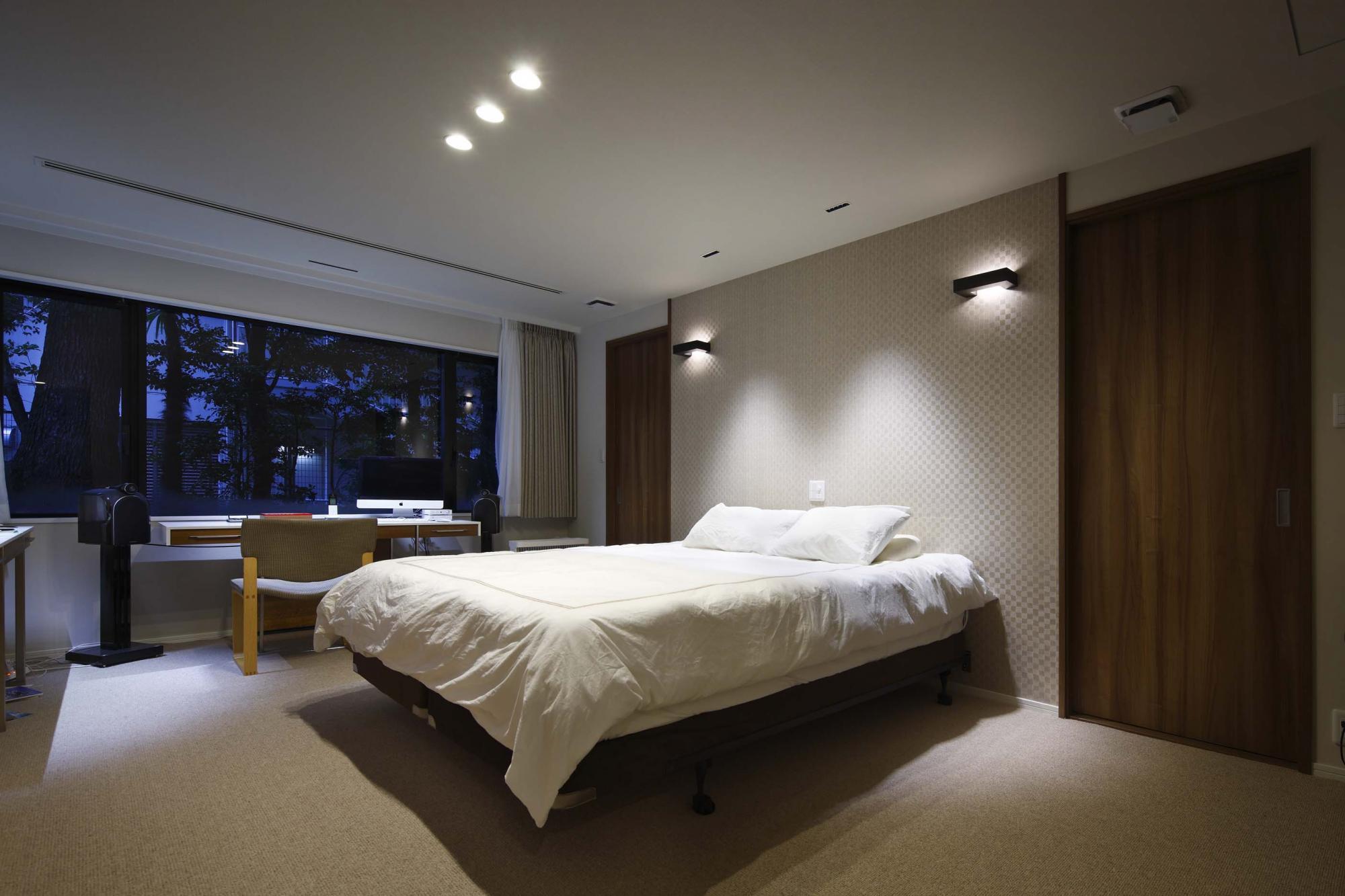 寝室はホテルのようなカーペット敷きに。ベッド背面の壁には光沢のある網代柄の白いクロスを貼って部屋のアクセントにした。またベッド背面の2つの扉は、ウォークインクロゼットへと続いている。