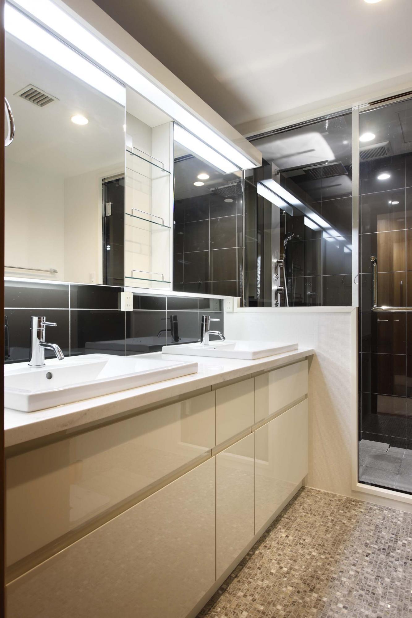 オーダーメイドの洗面化粧台。洗面前部のタイルはシャワールームと同じブラックのタイルを使用して統一感を出し、床はグレー系のモザイクタイルを貼っている。