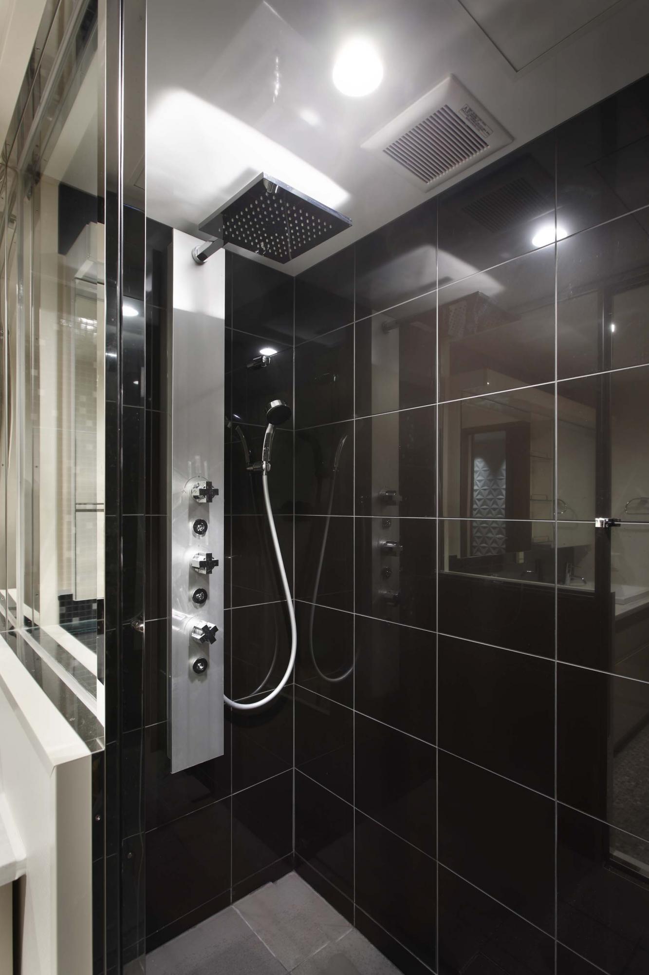 ご夫婦専用のシャワールームはブラックタイルの壁でシックに演出。リラックス効果の高いオーバーヘッドシャワーを採用した。