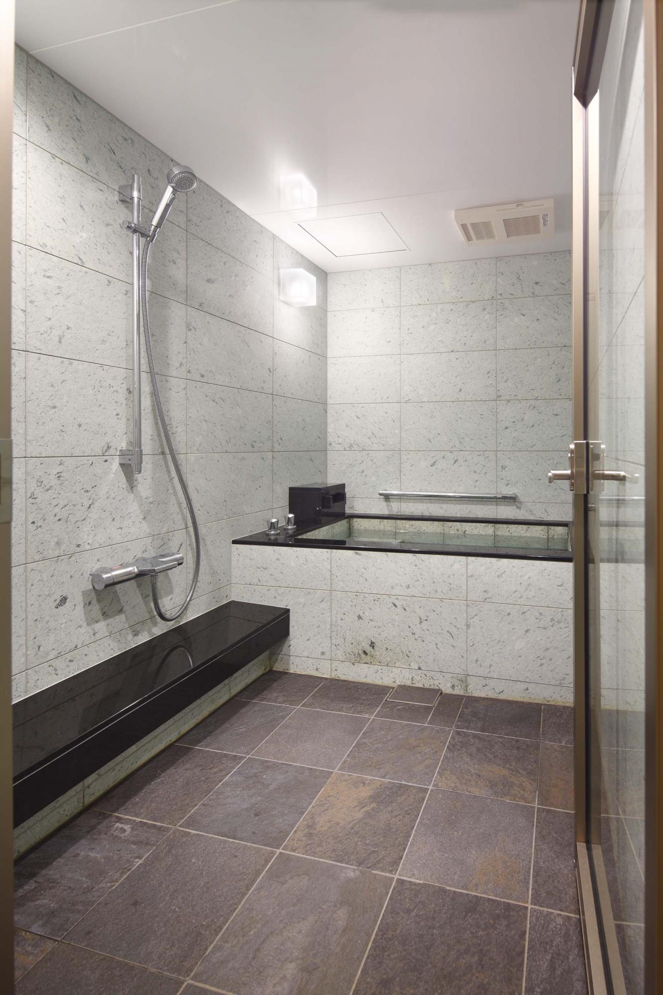 バスルームの扉は透明ガラスで視線を通し、明るさと広がりを。壁面と浴槽は水に濡れると緑帯びて美しい十和田石を貼って仕上げた