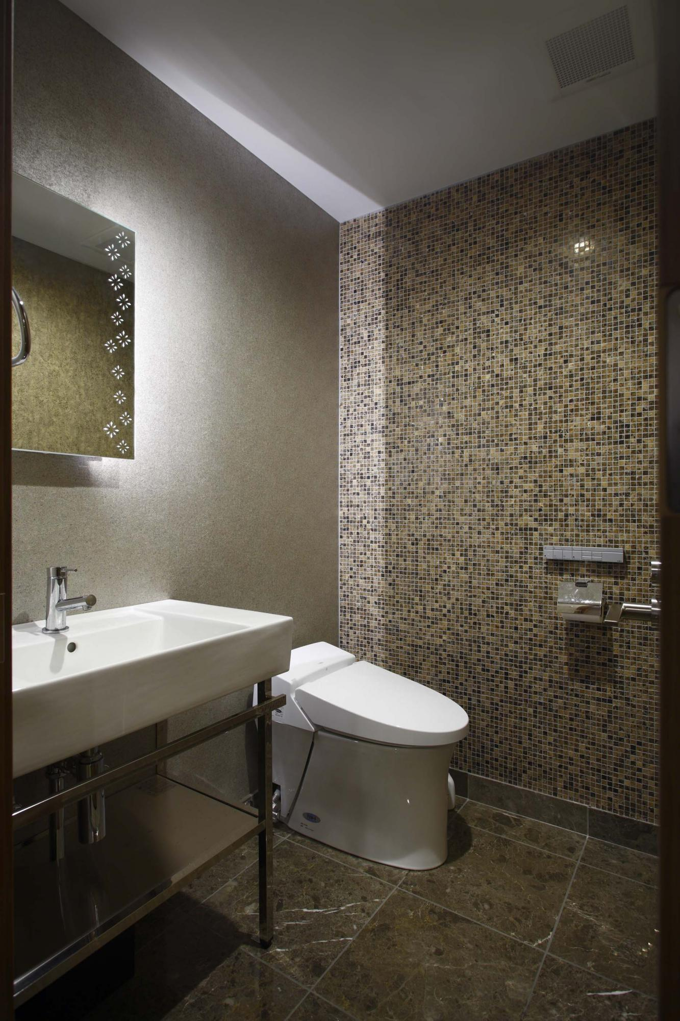 玄関ホールのすぐ左手にあるトイレはクロスにこだわり、一面はご主人がロサンゼルスから持参したデザインクロスを貼り、もう一面はモザイクタイルを使用。またミラーの後ろに間接照明を組み込み、壁に陰影をつけて雰囲気を出した。