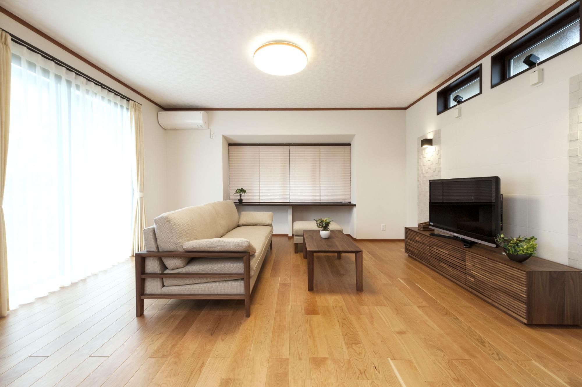 和室だった部分を広々としたリビングに変更。写真正面のカウンターデスクは造作し、開口部には桜色した和紙調のプリーツスクリーンを設置。 ソファやテーブルなどの家具は内装にあわせてモダンな印象になるようにセレクトした。
