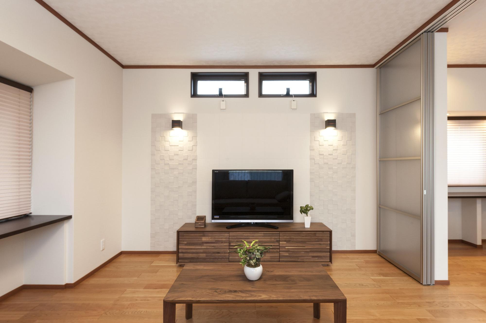 リビングのTVボードの背面壁には、部屋のアクセントになるエコカラットを。壁の上部には2連の窓を設け、通風と採光を確保した。 写真右のLDとの間に設置したパネルパーティションは当社オリジナル。上吊り式で床にレールがないので開けたときすっきりとして美しい。