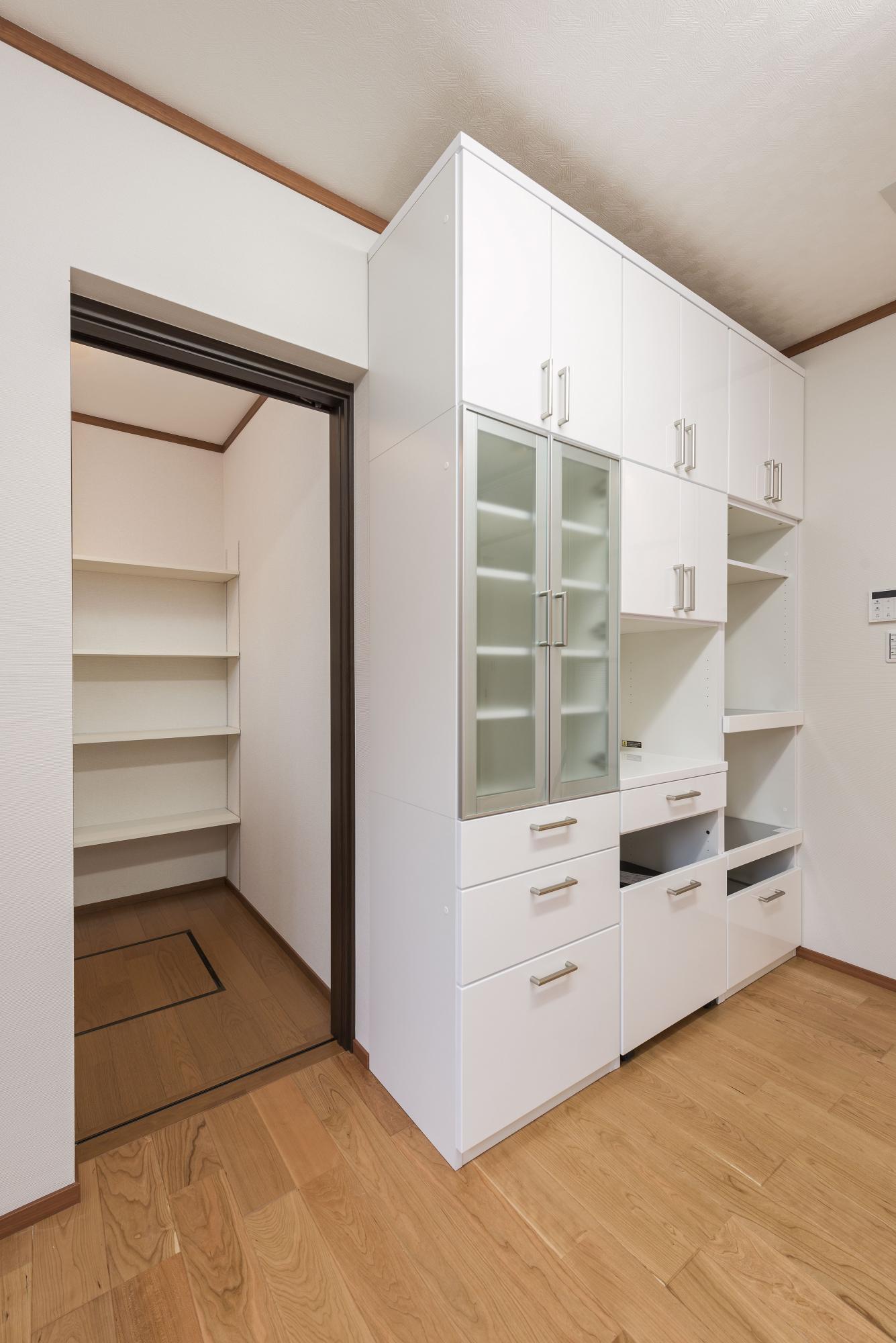 システムキッチンの後ろの引き戸を開けると、たくさんストックできる食品庫が。食器棚は既存のものを配置した。