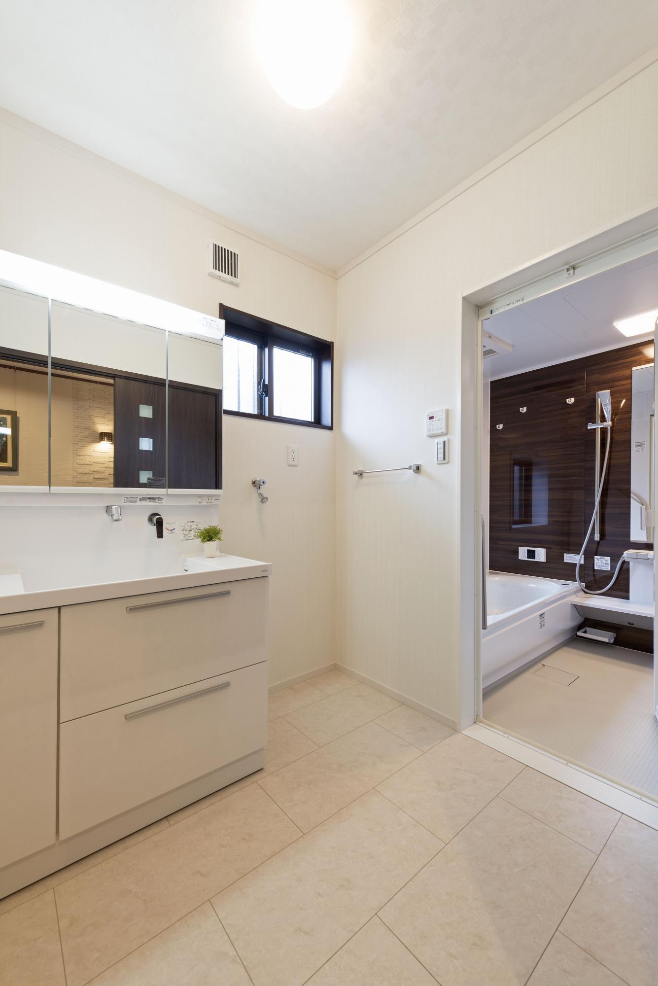 十分なスペースを確保した明るい洗面室&バスルーム。浴室には梅雨時や冬期などの洗濯のときに便利な暖房乾燥機を設置している。