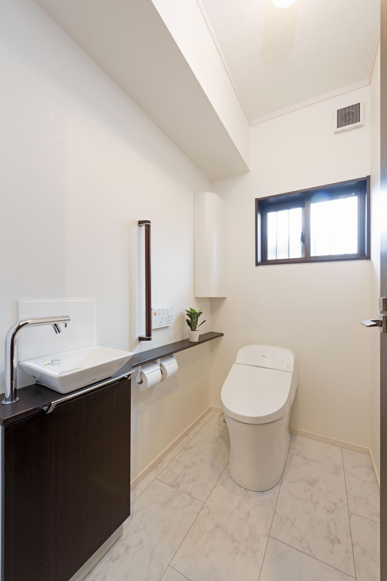 明るく清潔なトイレの床は、白の大理石調のフローリングに。ブラウン系の手洗いカウンターを設置し、壁にはコーナー収納を設けた。