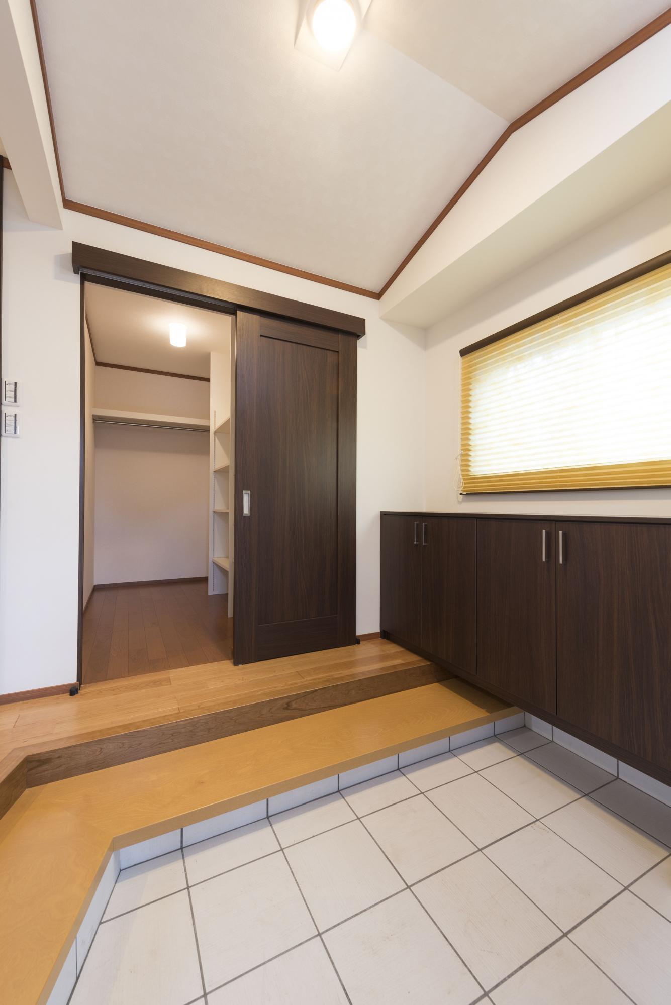 玄関の天井は和の雰囲気を出すために船底型に設計。 上がり框が高いため手前に式台を設け、上り下りが楽になるように配慮した。ご主人の希望で玄関の正面には大型のシューズクロークを配置し、コートを掛けたり、ベビーカーも置けてとても便利に。