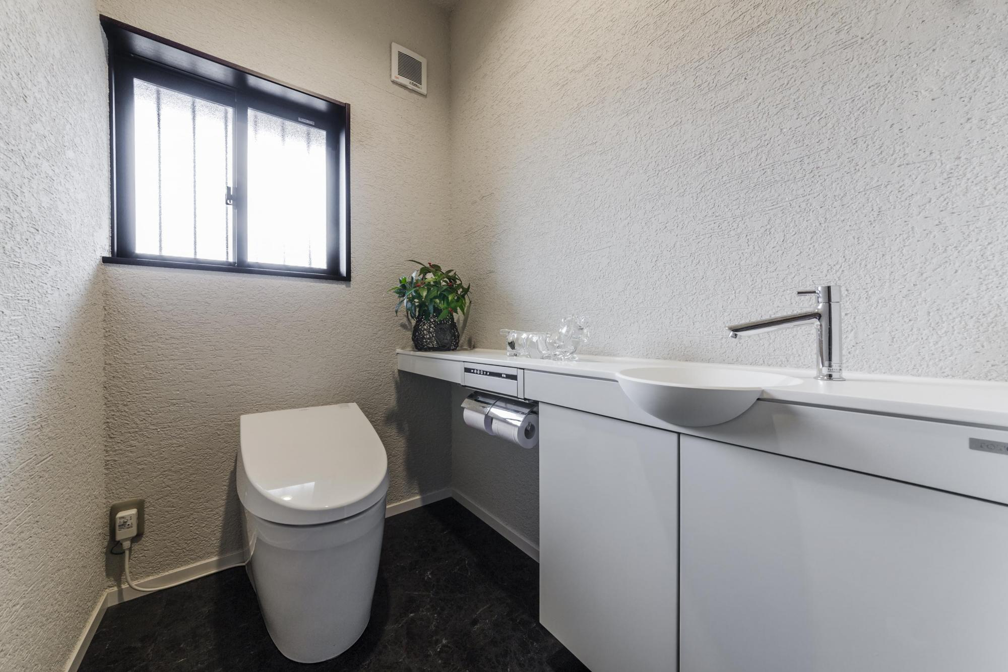 トイレも手洗いカウンターのあるゆったりしたものにした。自動洗浄機能付きでお手入れが楽。壁と天井の仕上げは、洗面室と同じく「シーサンドコート」。