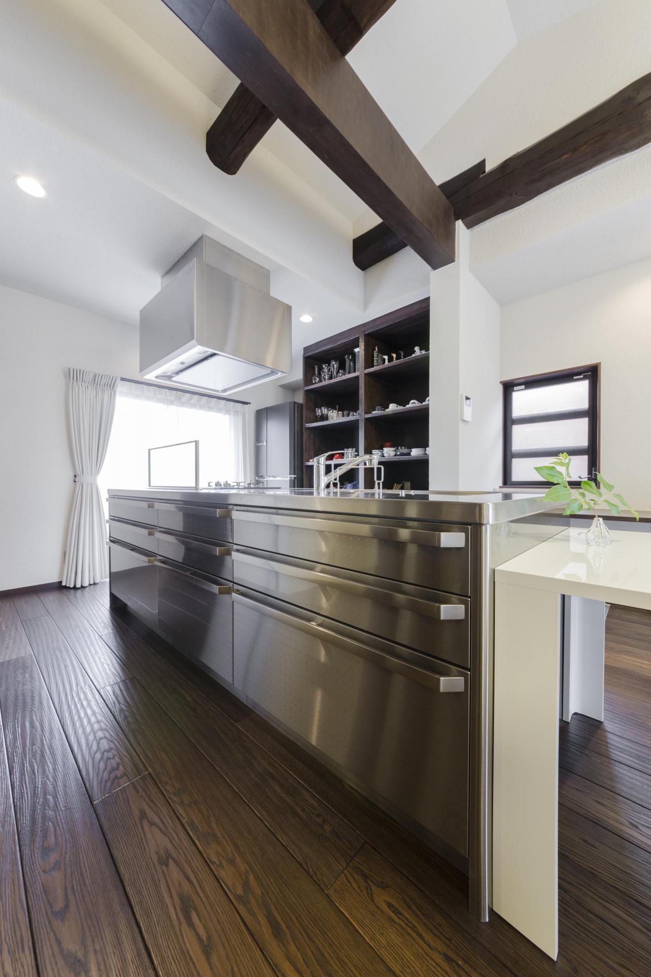 床はなぐり調のオーク。濃い色がステンレスのキッチンに似合う。隠す収納と見せる収納を組み合わせ、十分な収納量を確保した。