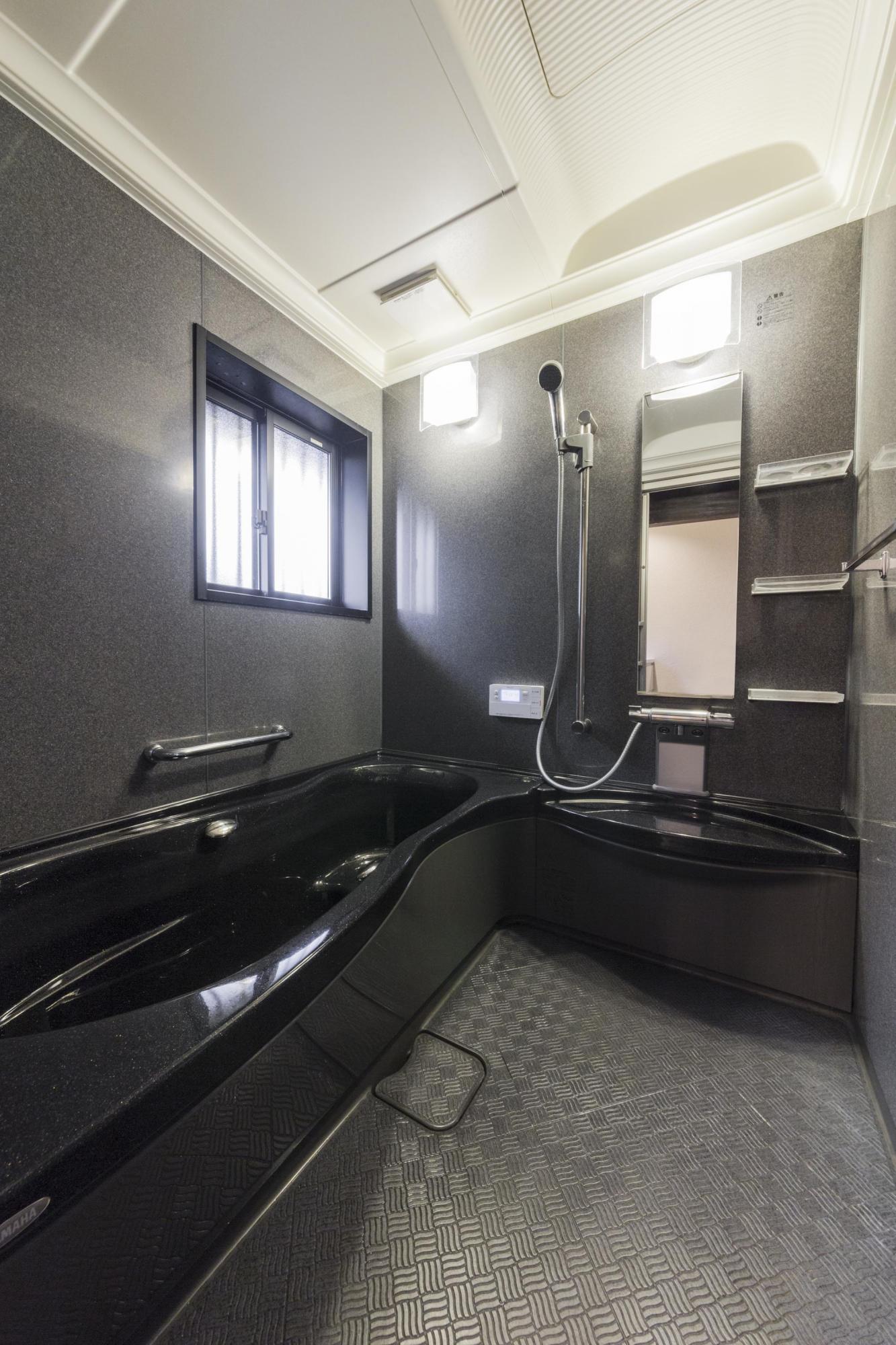 落ち着いた色合いの大型浴槽のある浴室。手入れが非常に楽になったとご家族に好評。