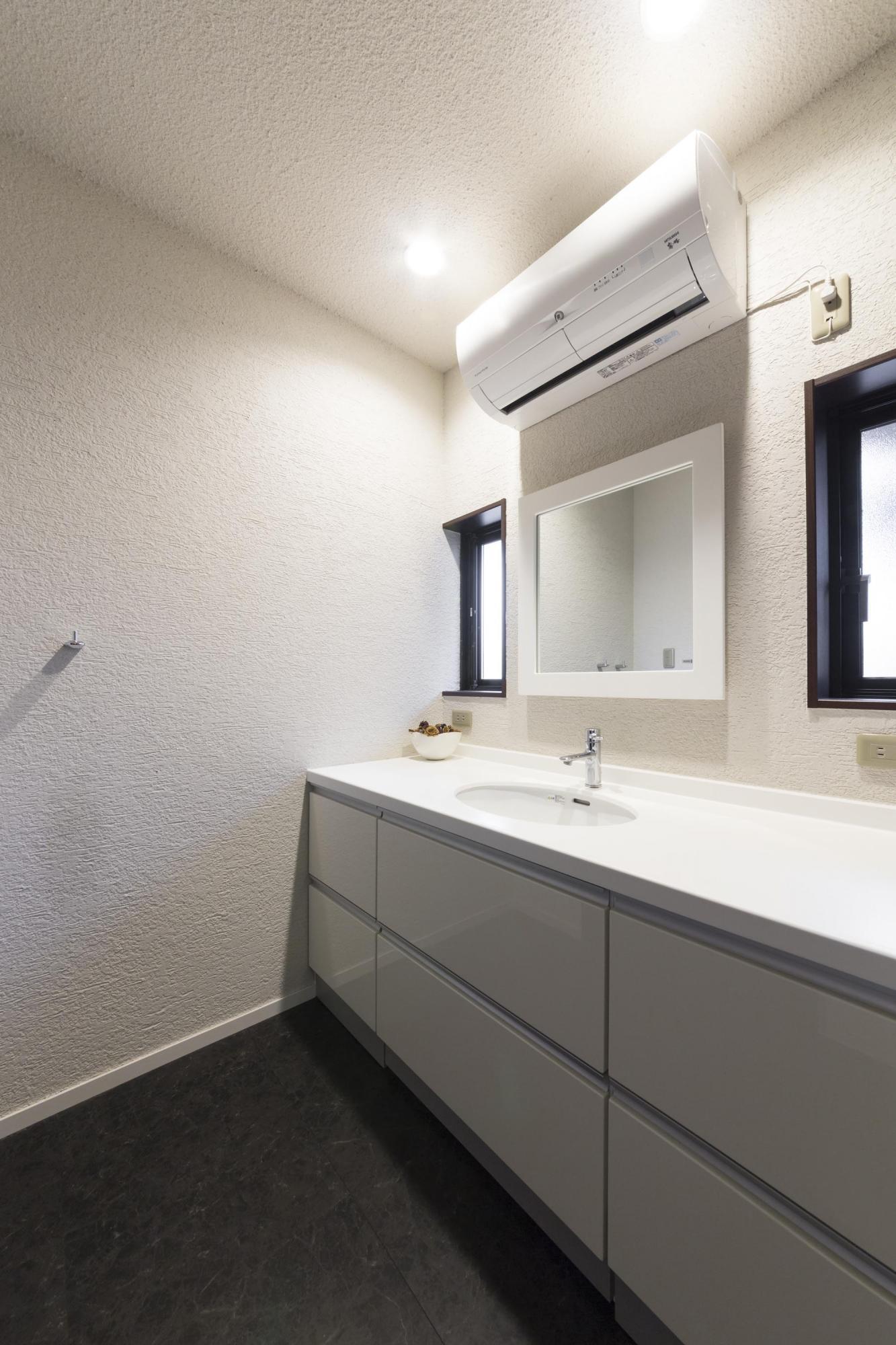 ゆったりと確保した洗面室。従来の倍以上の広さで、収納もたっぷりしている。自然素材を使いたいという要望を受け、壁と天井は貝殻や天然石を練り込んだ住友林業オリジナルの塗装材「シーサンドコート」で仕上げた。