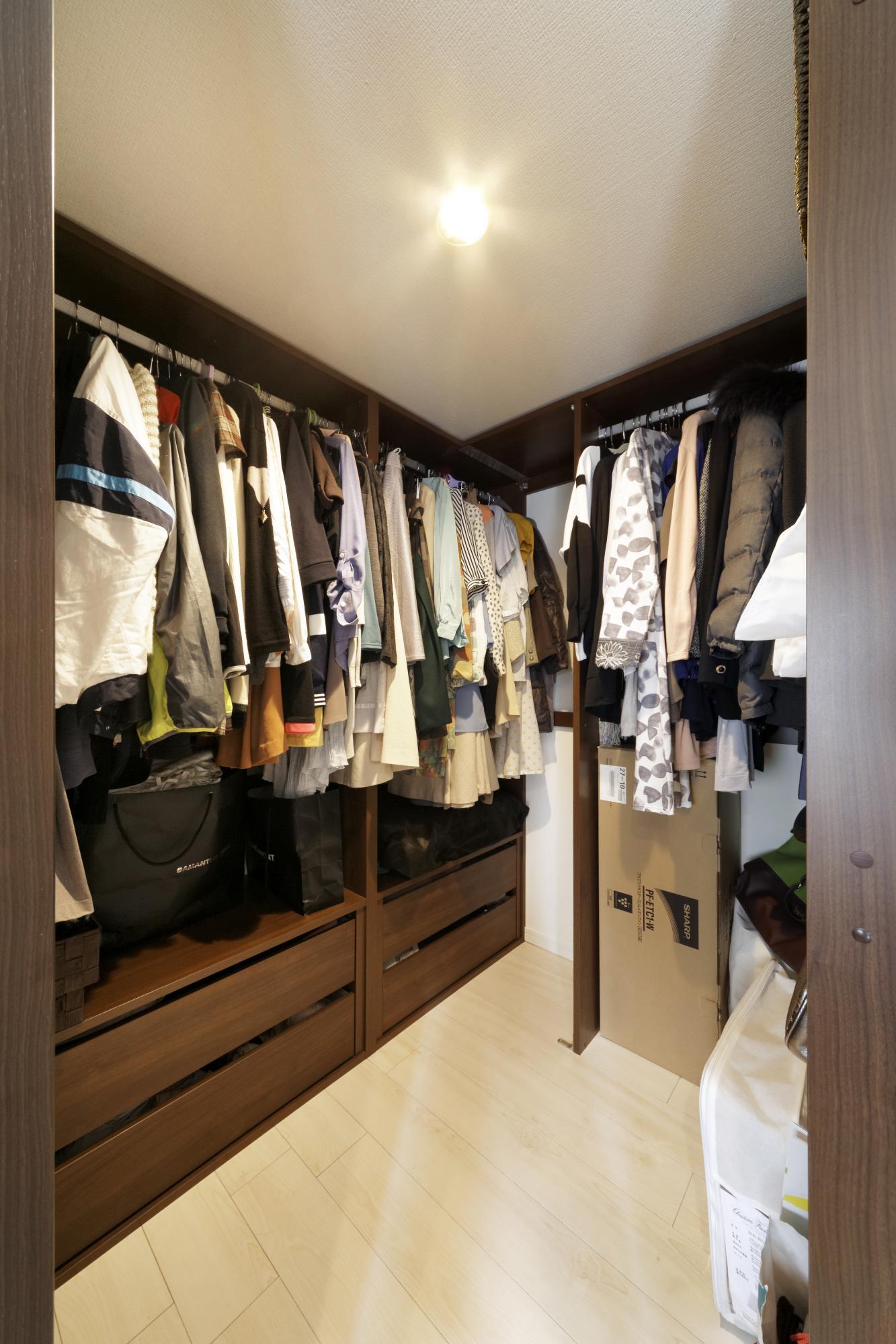 システム収納家具で使いやすく整えたウォークイン・クロゼット。床を上げ、この下にキッチンへの配管を集中して通した。